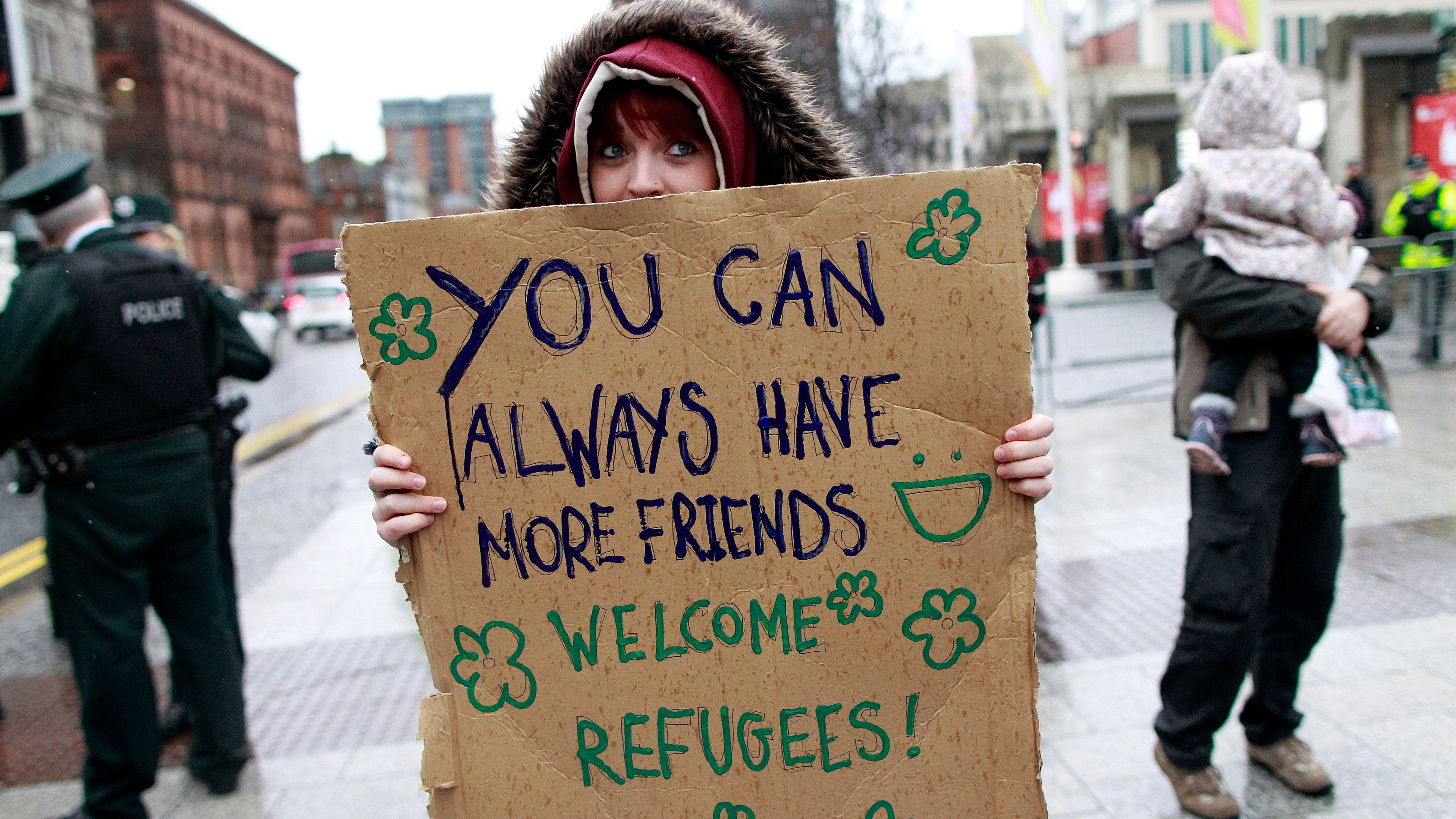 A  person joins the counter demonstration as they protest at the arrival of Anti-refugee rally outside Belfast city hall, Northern Ireland, Saturday, Dec. 5, 2015.  The anti-refugee protest was made up of mainly Loyalist supporters and was organized ahead of the arrival on December 12th of Syrian refugees to Northern Ireland.