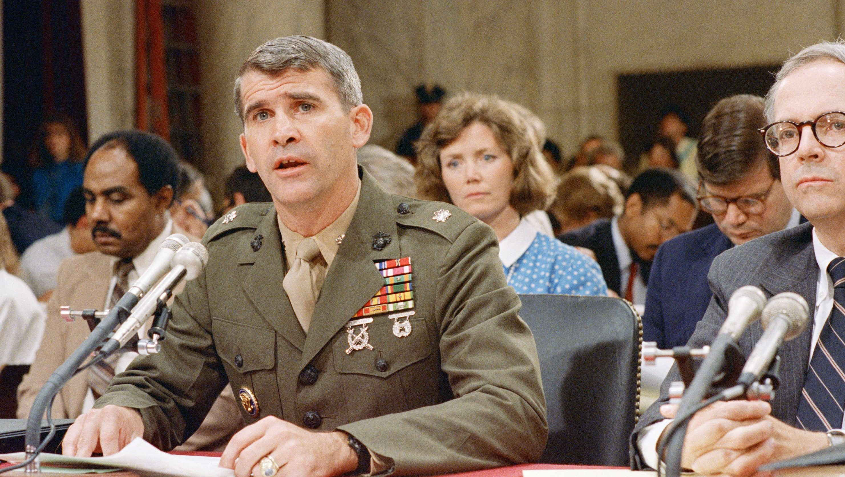 t. Col. Oliver North reads his opening statement at the start of his third day of testimony before a congressional committee holding hearings on the Iran-Contra affair on Capitol Hill in Washington, July 9, 1987. North?s wife Betsy looks on over his shoulder. (AP Photo/J. Scott Applewhite)