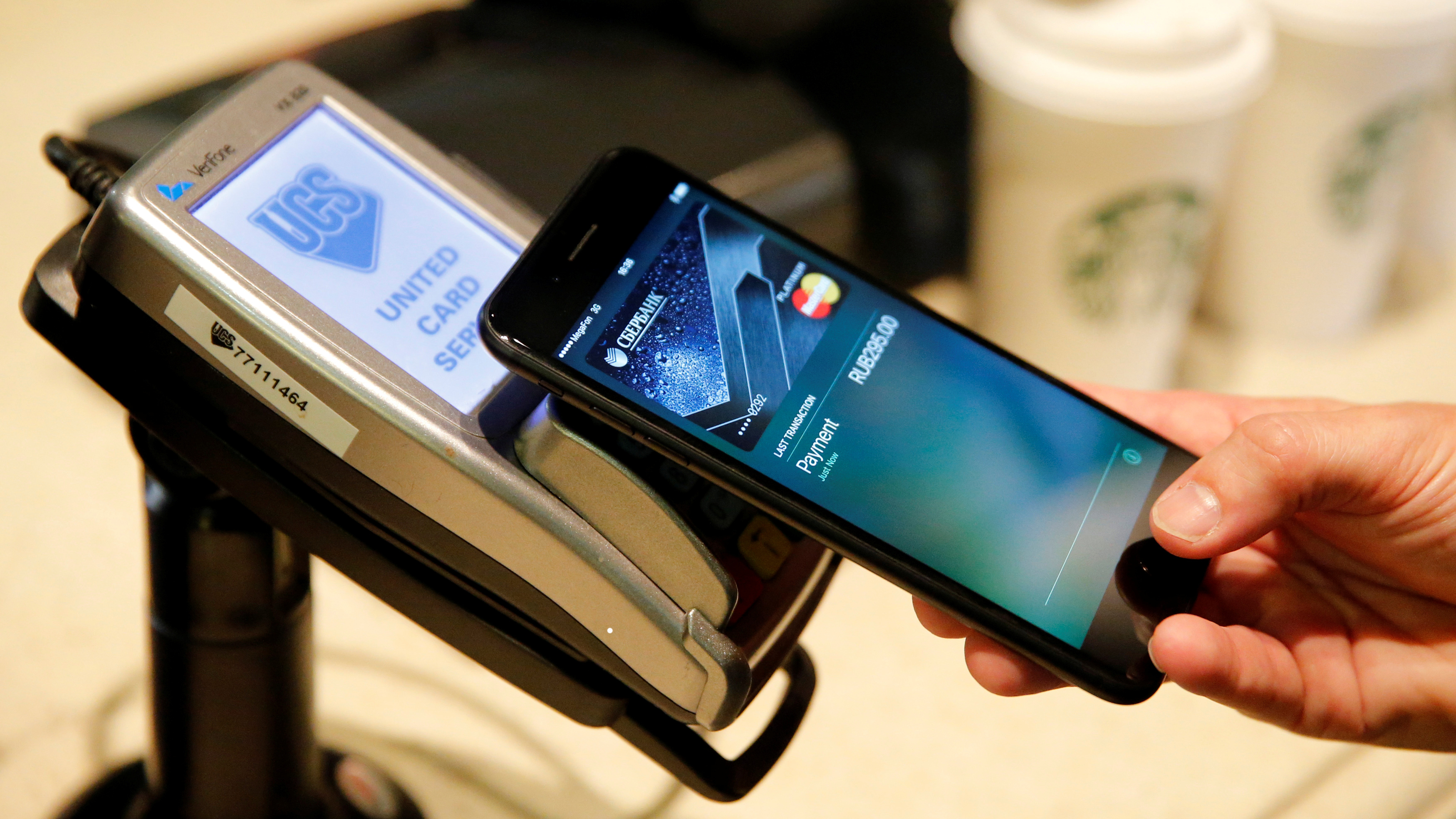 A man uses an iPhone 7 smartphone to demonstrate the mobile payment service Apple Pay at a cafe in Moscow, Russia, October 3, 2016. Picture taken October 3, 2016.   REUTERS/Maxim Zmeyev - S1BEUEYZNGAB