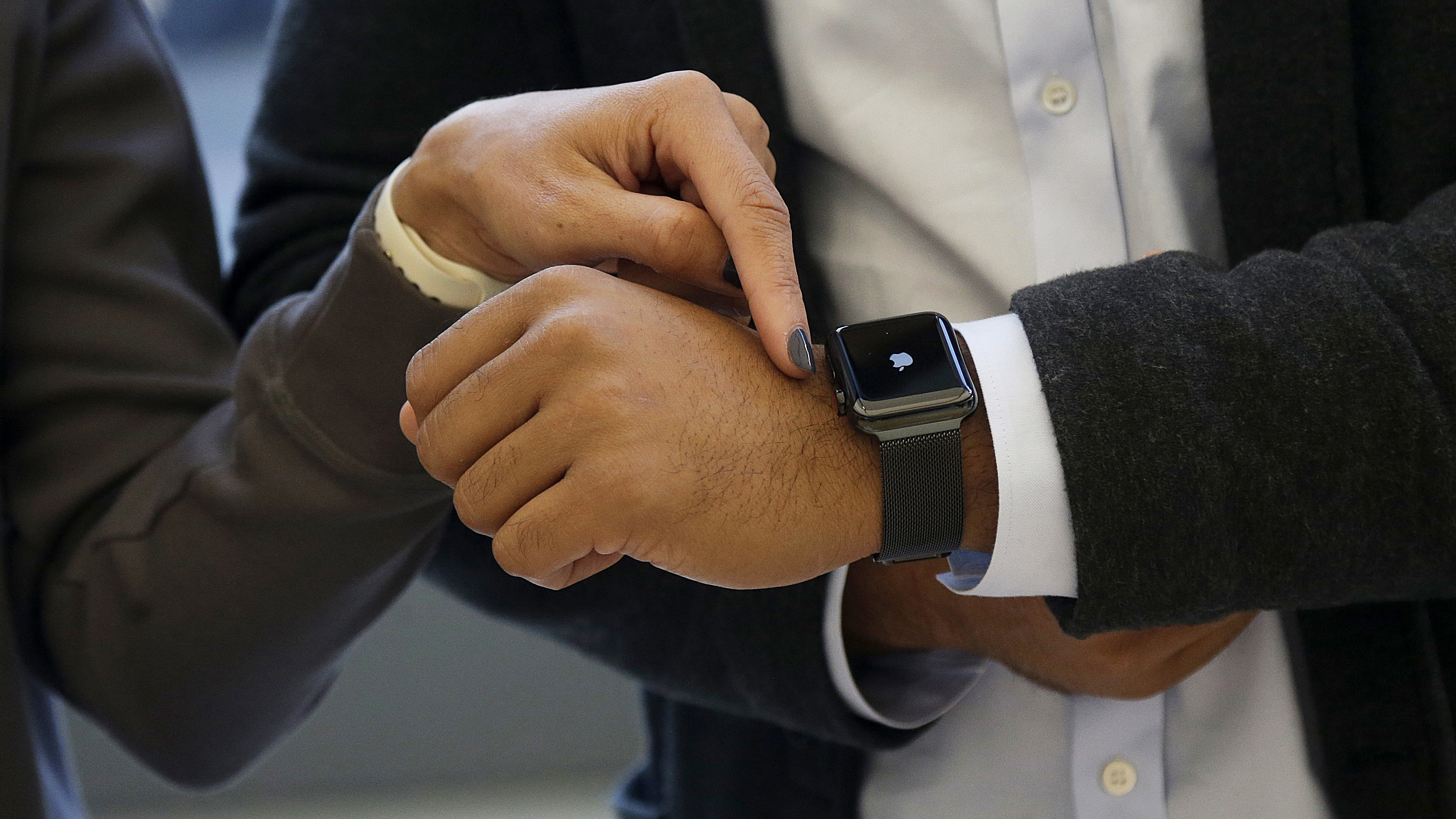 An Apple retail associate points toward a man's Apple Watch while assisting him at an Apple Store in San Francisco, Friday, Sept. 22, 2017. Many of Apple's newest products came out Friday. (AP Photo/Jeff Chiu)