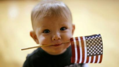 Dylan Curry, 11 months old, carries a U.S. flag in his mouth as he waits for his U.S. Army soldier father to return from Iraq before a ceremony at Fort Carson in Colorado Springs, Colorado February 12, 2009. About 280 soldiers from the 3rd Brigade Combat Team, 4th Infantry Division returned following their 15-month deployment to Iraq.