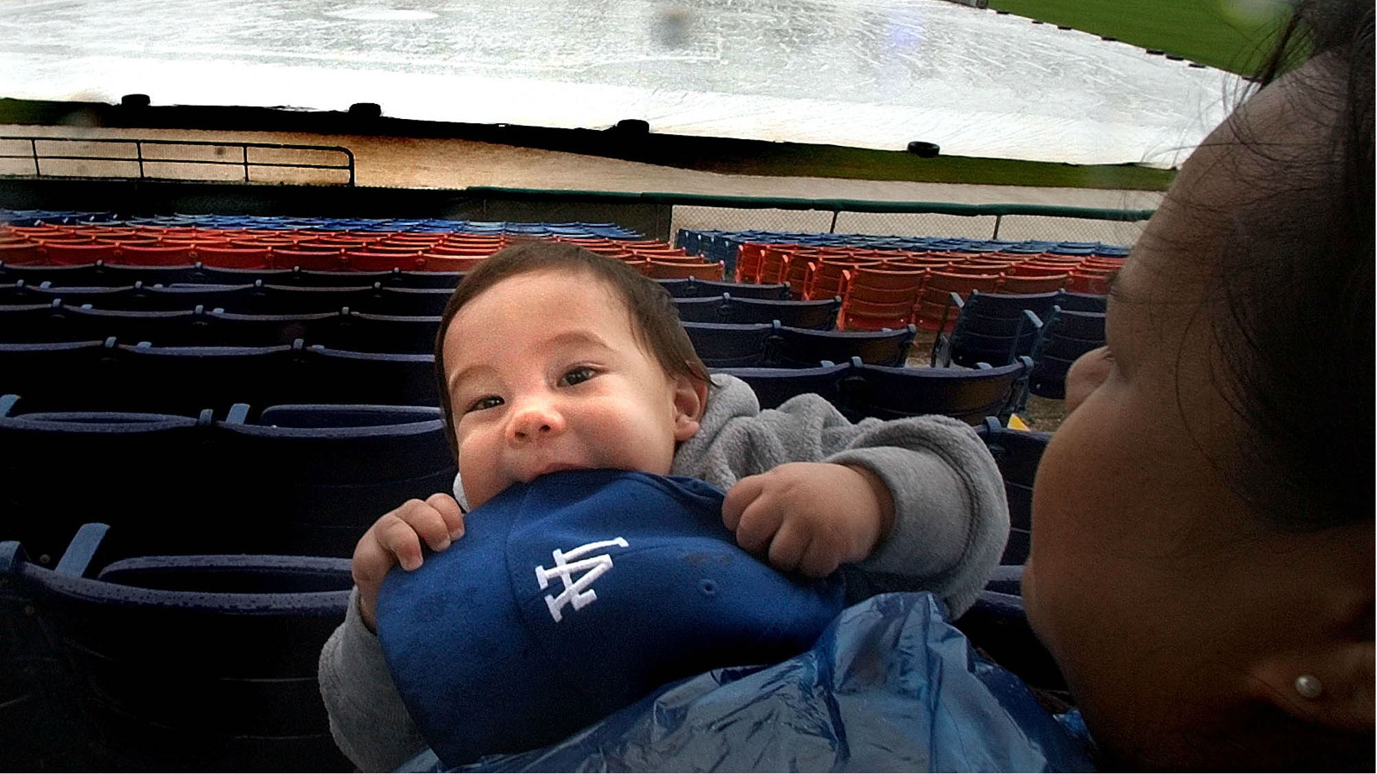 A baby chewing on on a baseball hat.