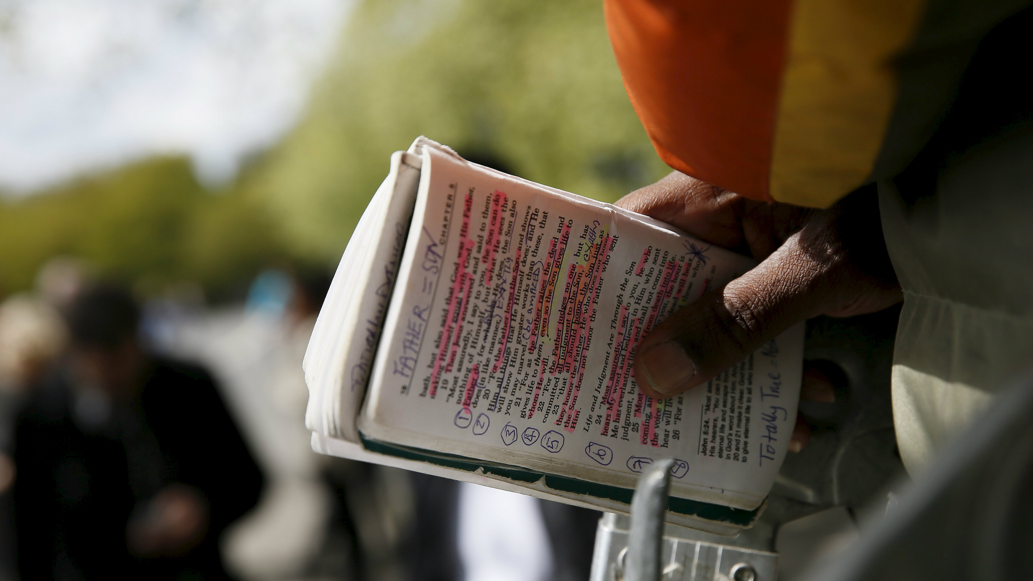 Man holding annotated bible