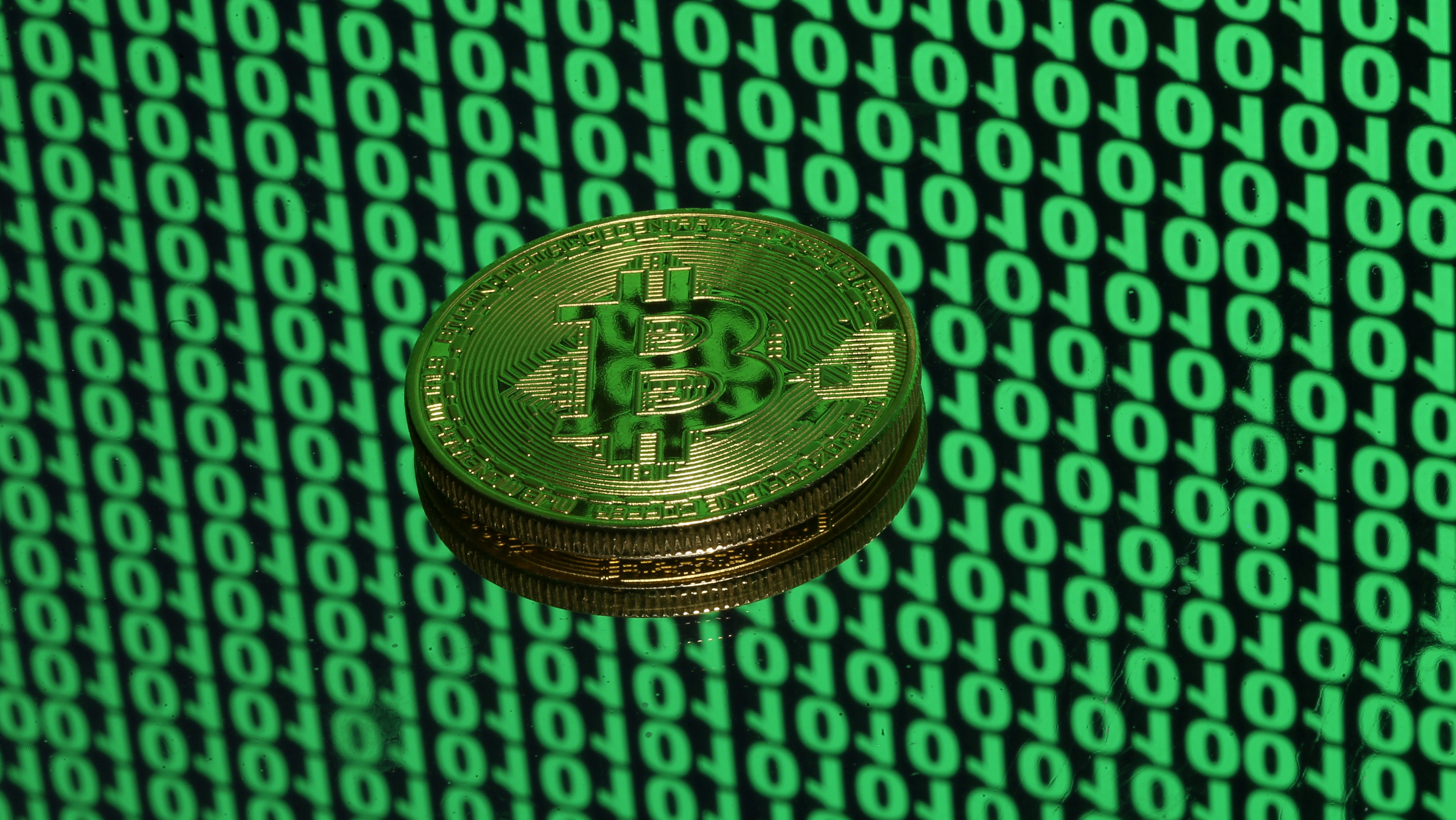 A token of the virtual currency Bitcoin is seen placed on a monitor that displays binary digits in this illustration picture, December 8, 2017. Picture taken December 8.