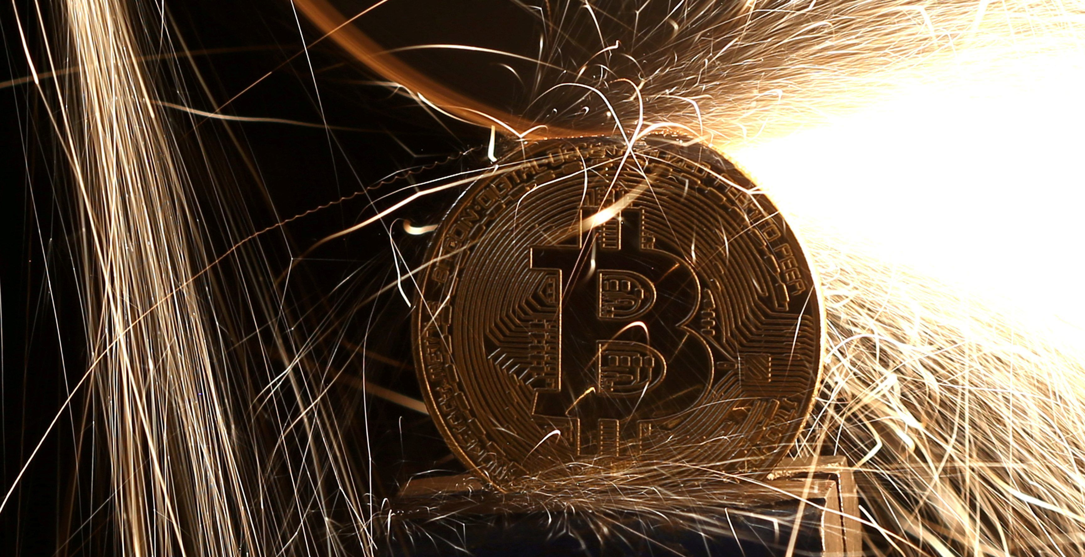 FILE PHOTO: Sparks glow from broken Bitcoin (virtual currency) coins in this illustration picture, December 8, 2017.