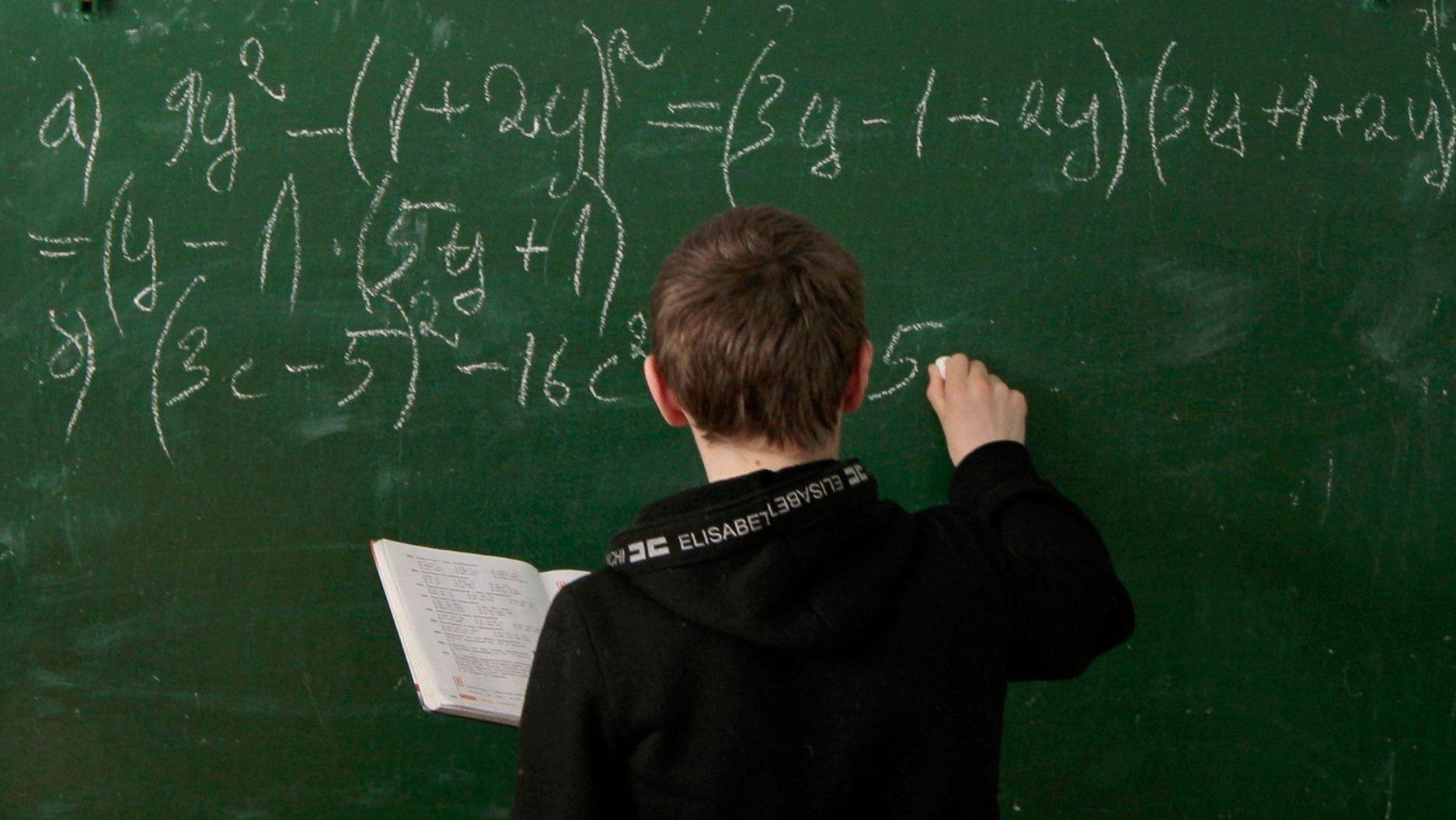 A student writes on a blackboard