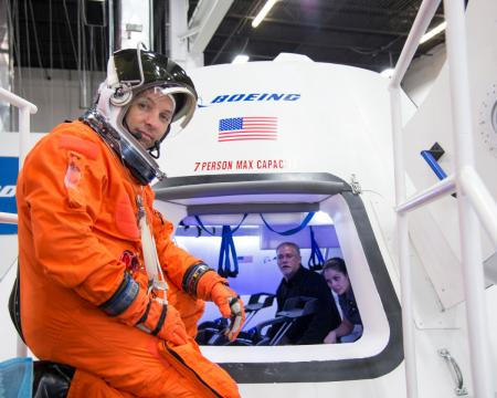 """NASA astronaut Randy Bresnik prepares to enter Boeing's CST-100 spacecraft for a fit check evaluation at the company's Houston Product Support Center in this undated image. NASA will partner with Boeing and SpaceX to build commercially owned and operated """"space taxis"""" to fly astronauts to the International Space Station, ending U.S. dependence on Russia for rides, officials said on Tuesday."""