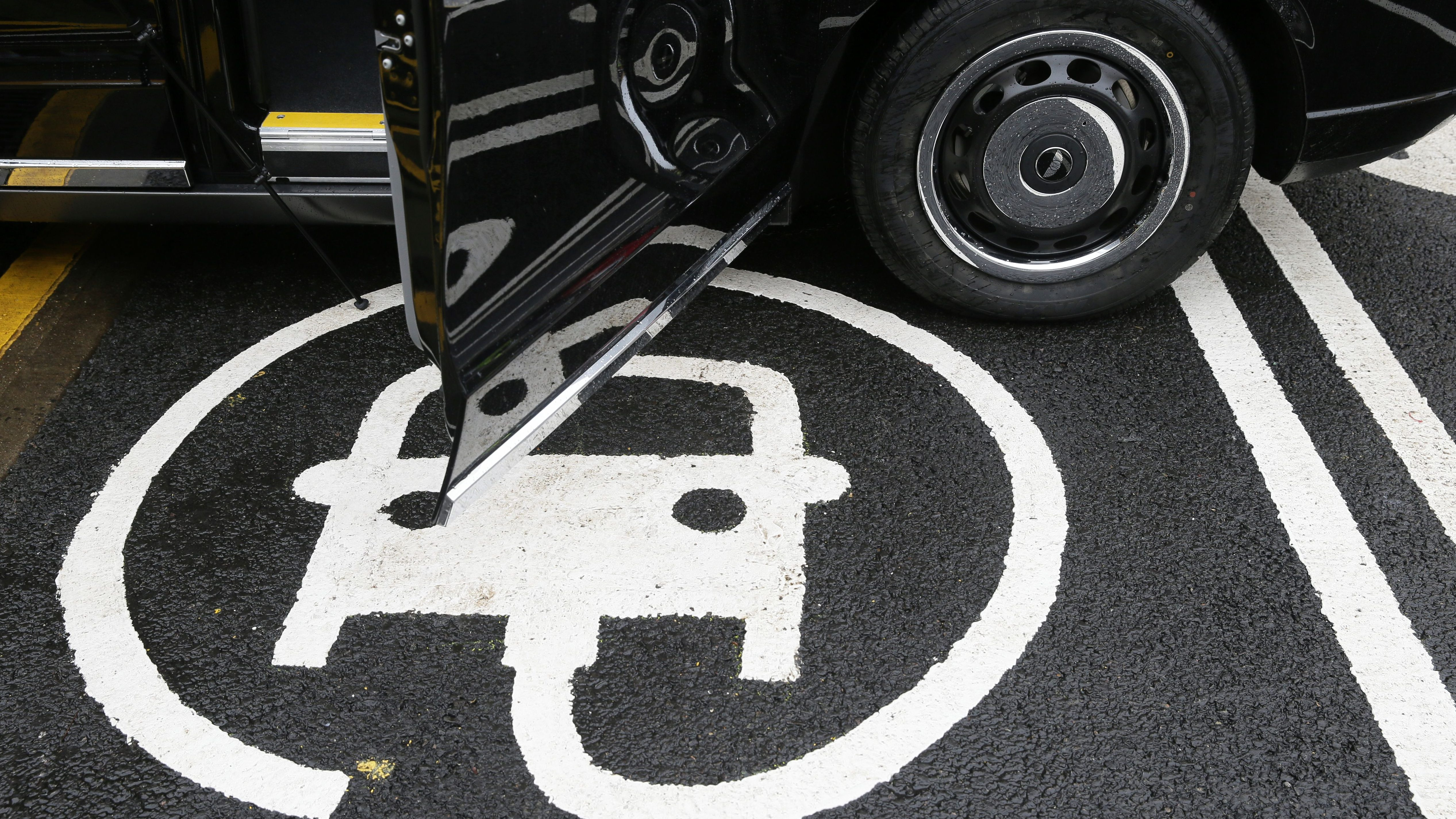 The electric car recharging sign, as a new TX Cab London taxi is parked at a charging station during a media opportunity at a Shell petrol station on Holloway road, in London, Wednesday Oct. 18, 2017, 2017. Only days after Shell agreed to buy electric vehicle charging firm NewMotion, Shell are opening three charging stations Wednesday with more expected by the end of the year.  (AP Photo/Tim Ireland)