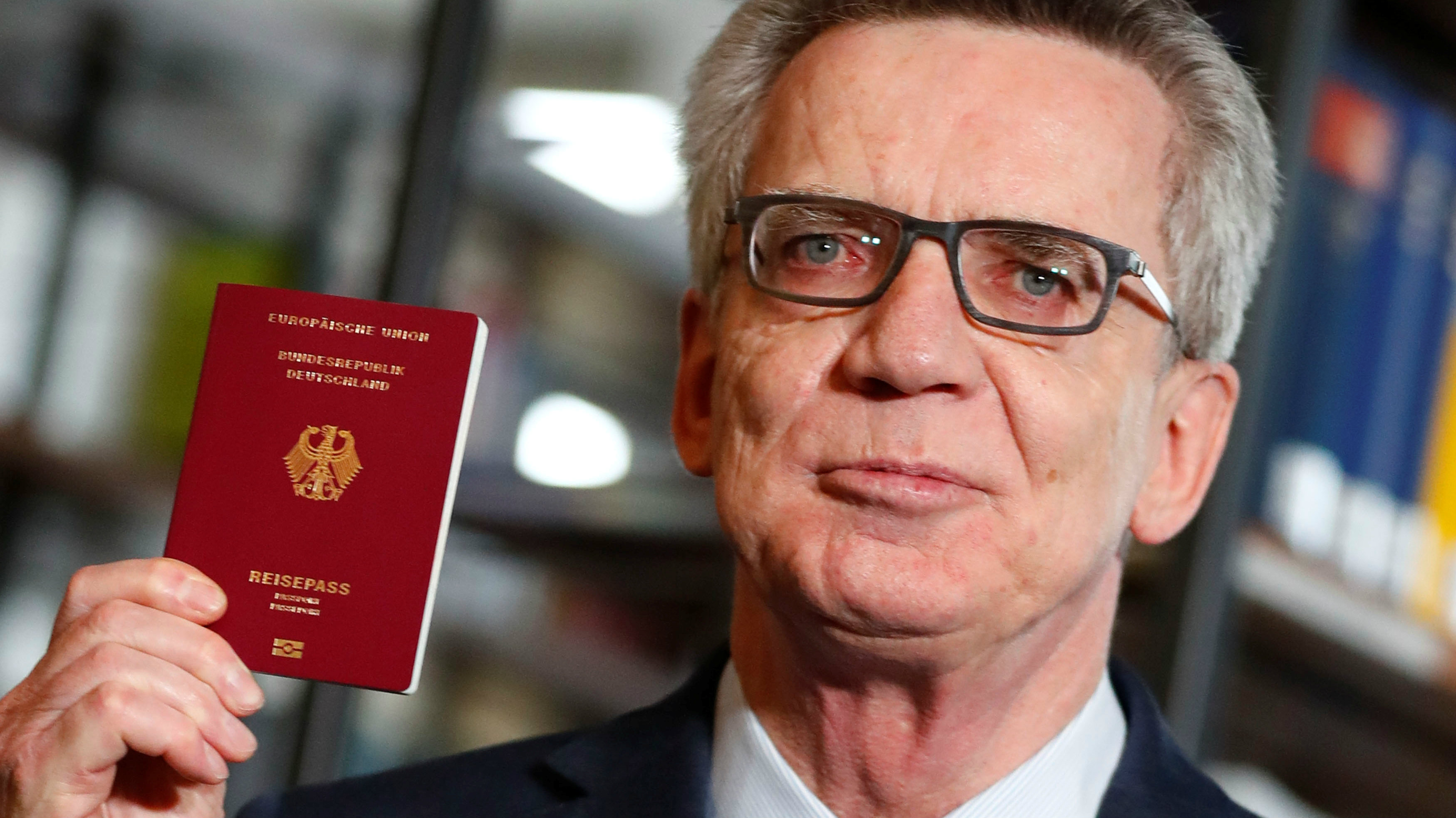 German Interior Minister Thomas de Maiziere presents the new electronic passport in Berlin, Germany, February 23, 2017.