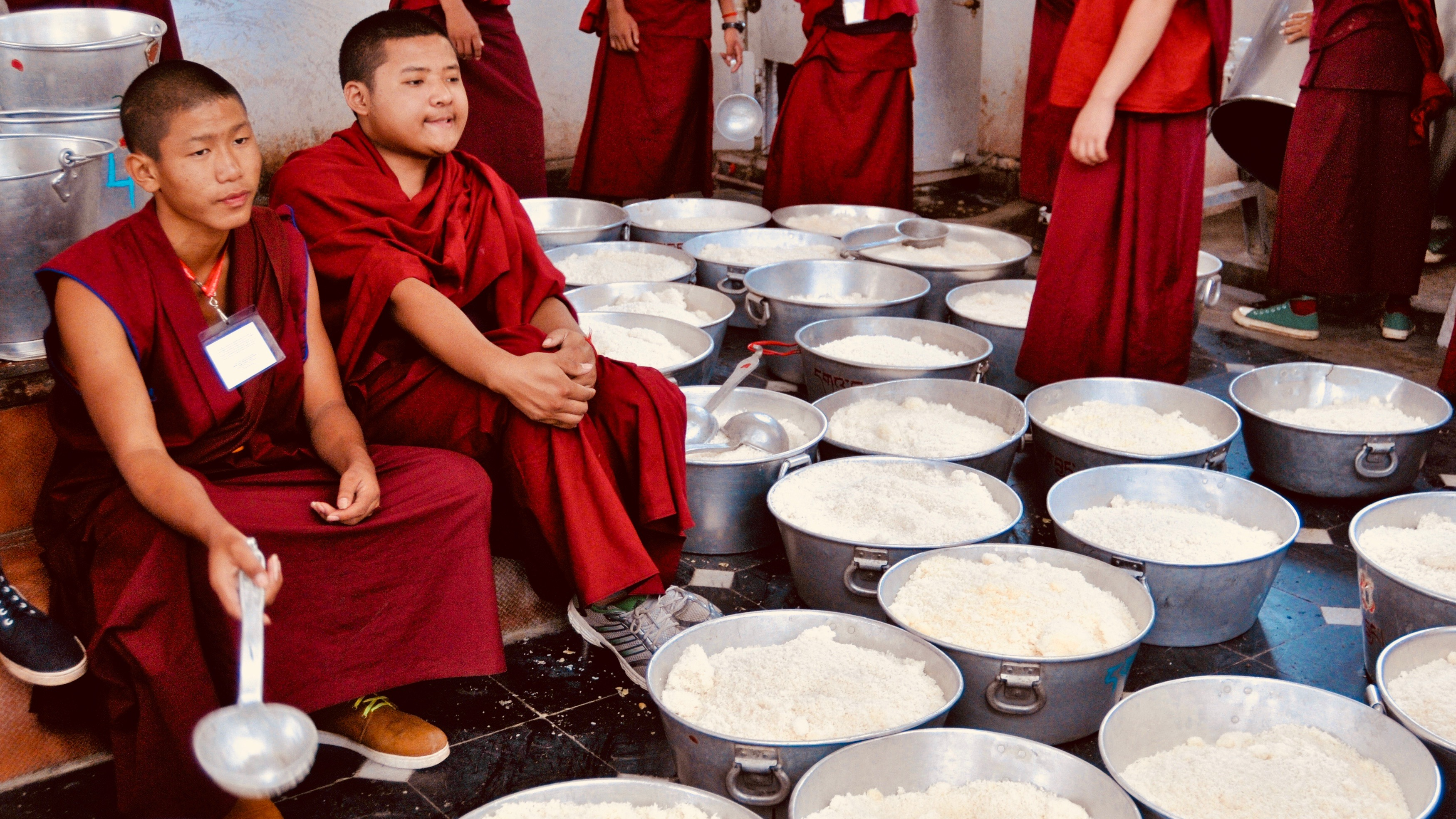 Buddhist monks serve food at monastery.