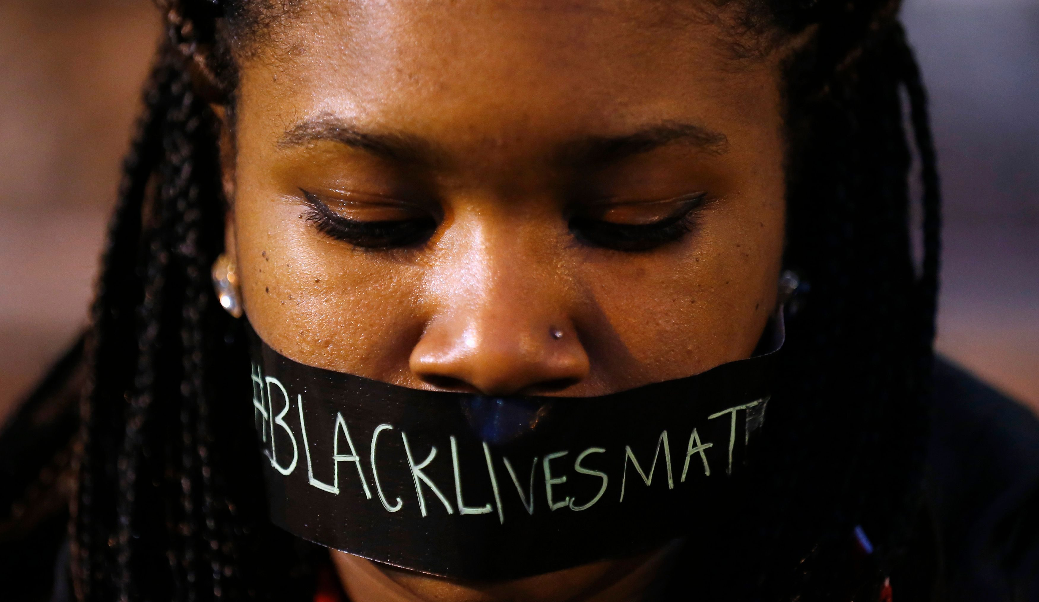 A protester wears tape over her mouth during a silent demonstration in St. Louis, Missouri.