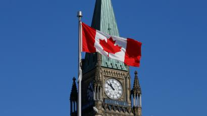 A Canadian flag flies in front of the Peace Tower on Parliament Hill in Ottawa, Ontario, Canada,