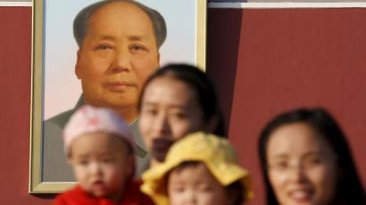 Two women and their babies pose for photographs in front of the giant portrait of late Chinese chairman Mao Zedong on the Tiananmen Gate in Beijing November 2, 2015. China must continue to enforce its one-child policy until new rules allowing all couples to have two children go into effect, the top family planning body said. The ruling Communist Party said last week that Beijing would loosen its decades-old one-child policy. The plan for the change must be approved by the rubber-stamp parliament during its annual session in March.