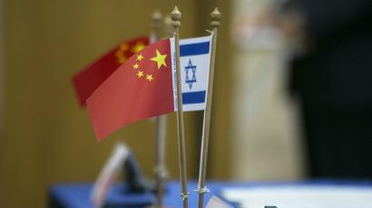 Chinese and Israeli flags are seen on a table during a signing ceremony marking a launch by Tel Aviv University and Beijing's Tsinghua University of a $300 million joint centre for innovative research and education, in Tel Aviv May 20, 2014. China's purchase, announced on Thursday, of a controlling stake in Israel's largest food maker reflects a broader surge in Chinese investment in an economy largely tethered to Western markets.