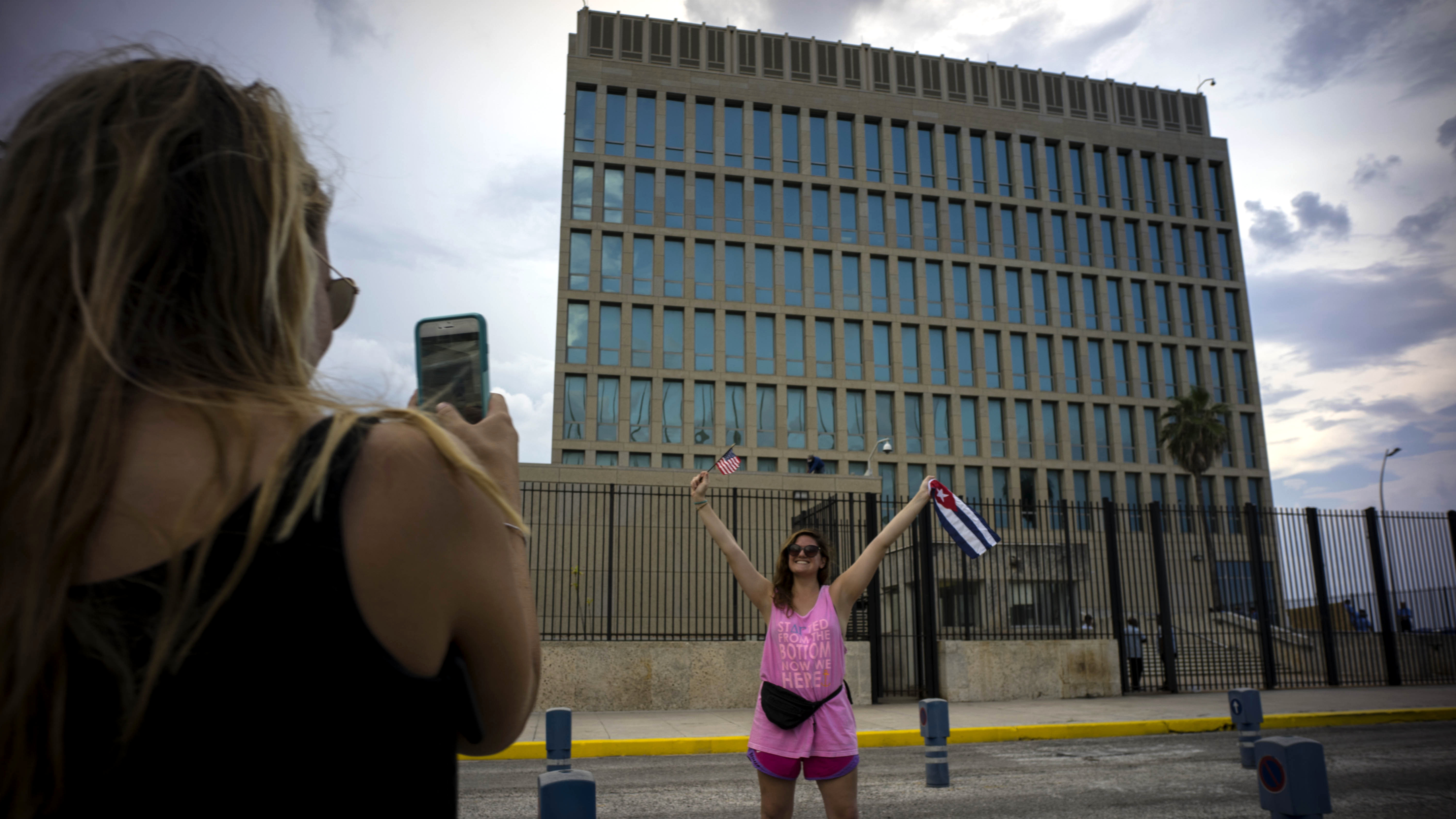 FILE- In this Aug. 11, 2015 file photo, US Citizen Jordan Graddis, 24, left, takes a photo of Emily O'connell, 24, as she holds a US and a Cuban flag in front of the U.S. embassy in Havana, Cuba. On Friday, June 16, 2017, President Donald Trump will give America's Cuba policy its second 180-degree spin in three years. Speaking from Miami, Trump's expected to revive the Cold War goal of starving Cuba's communist system of cash while inciting the population to overthrow it.