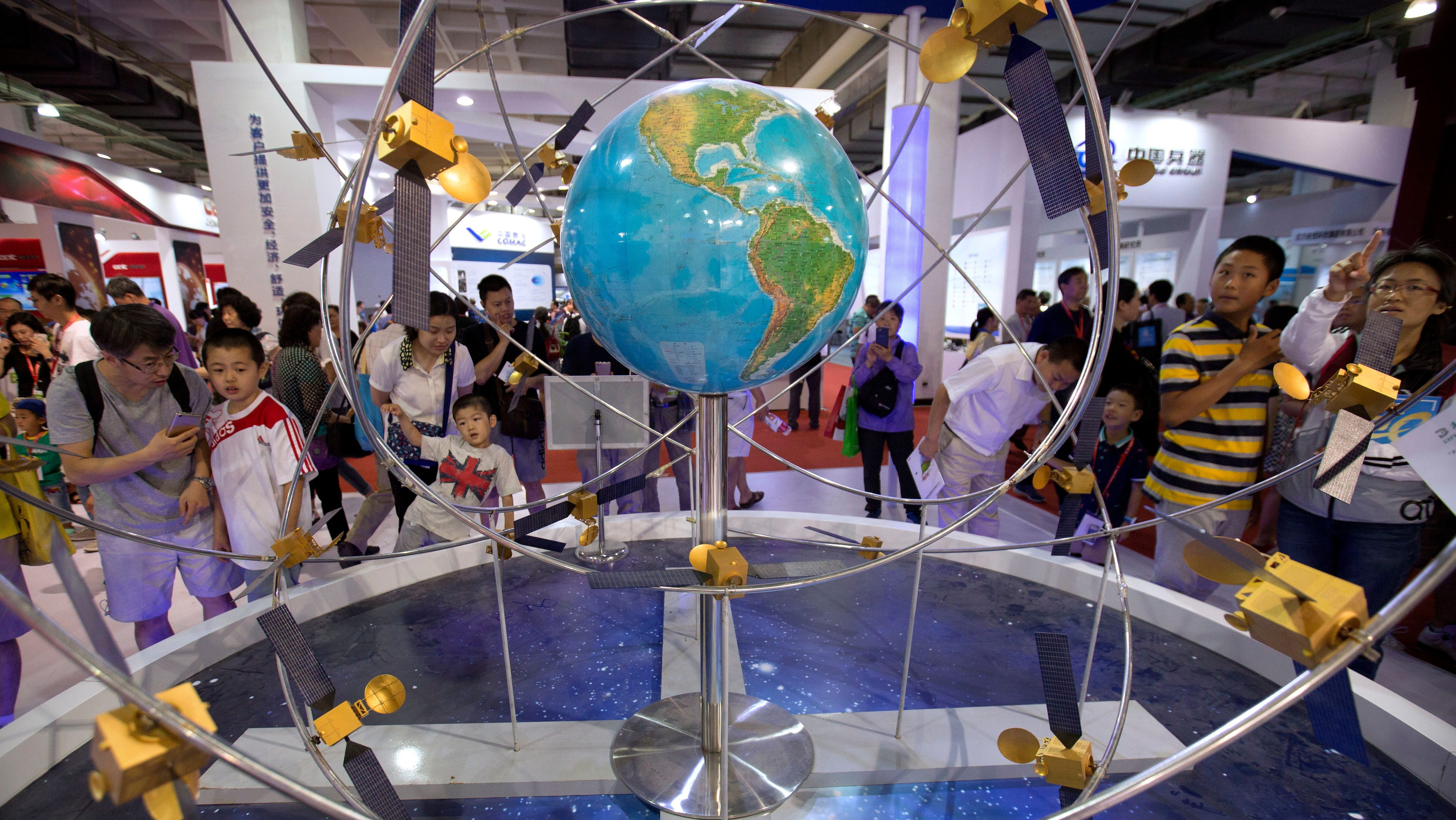 Visitors look at a mockup of China's homegrown Beidou satellite navigation system at the China Beijing International High-Tech Expo in Beijing, Saturday, June 10, 2017. The annual forum and exhibition is a showcase for Chinese domestic technology companies and innovation. (AP Photo/Mark Schiefelbein)