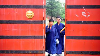 A female Taoist priest (L) talks on her mobile phone as she walks with a fellow priest towards a wooden door at Yuquan Yuan (Jade Spring Taoist Temple) at the foot of Mount Hua, in Huayin, Shaanxi province July 4, 2012. More than 60 priests from all over China gathered at this temple for a two-month course of Taoist music, which is an essential element to many Taoist ceremonies, local media reported. Picture taken July 4, 2012. REUTERS/Rooney Chen