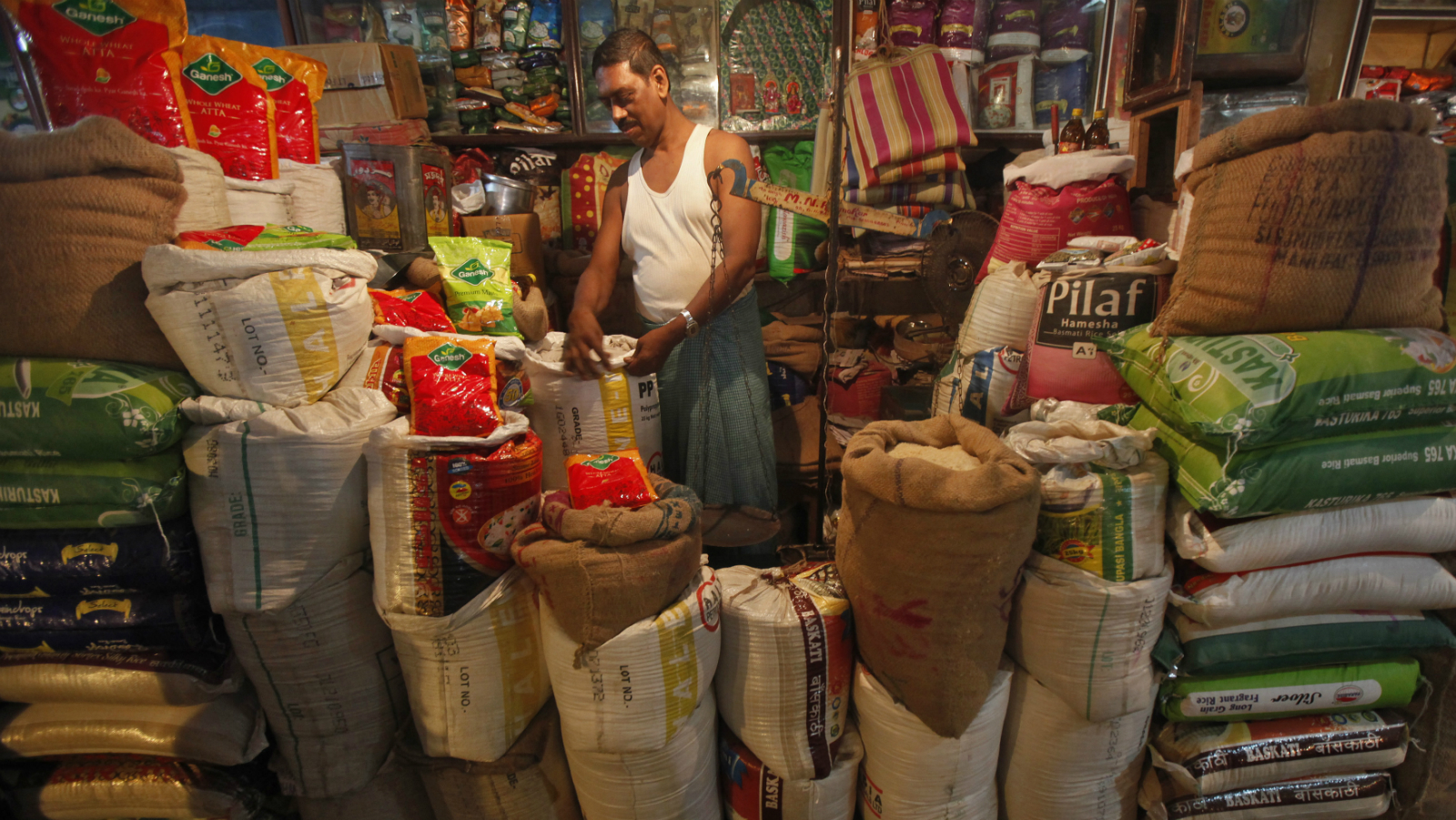 """The owner of a """"Kirana"""" or mom-and-pop grocery store arranges a rice sack in Kolkata October 24, 2013. India's finance minister is finding it harder and harder to meet the government's budget promises and may sweep as much as $15 billion in subsidy costs into next year's accounts to ensure he hits fiscal targets ahead of national elections, ministry officials say."""