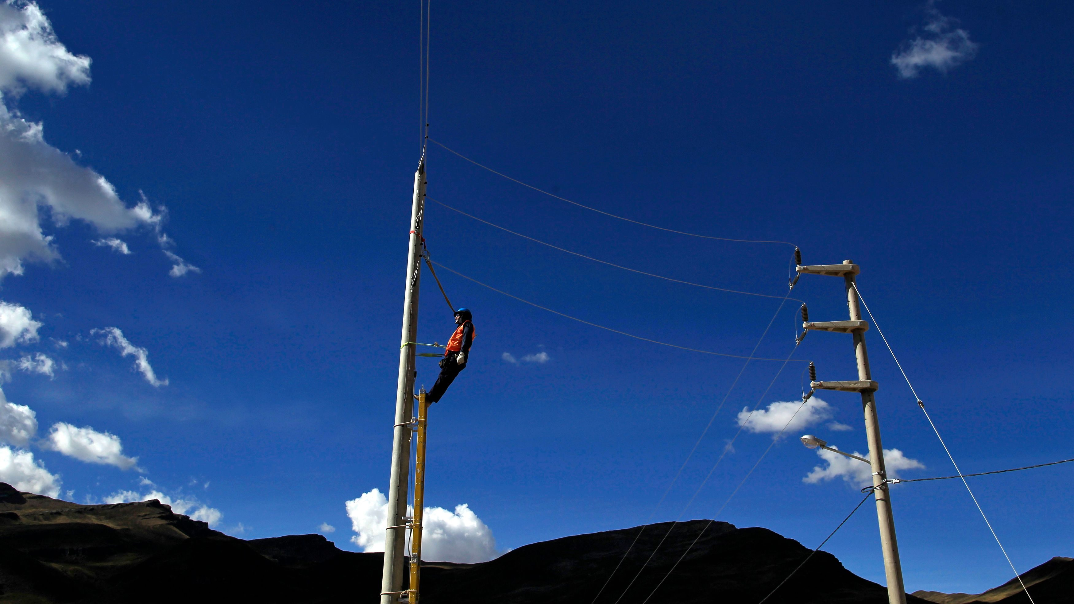 """A worker inspects an electrical pole in the new town named """"New Morococha,"""" in the andean city of Junin, June 18, 2012. High in the Andes mountain range, a Chinese mining company is now in the housing construction and demolition business as it works to relocate a Peruvian town that sits in the way of its $2.2 billion Toromocho copper mine. By late July, state-owned miner Chinalco says it will finish building a new city of paved roads and multi-story homes for 5,000 people currently living on the side of a giant red mountain of copper 15,000 feet (4,500 meters) above sea level. Picture taken June 18, 2012. To match Feature PERU-MINING/CHINALCO REUTERS/Pilar Olivares (PERU - Tags: POLITICS ENVIRONMENT TPX IMAGES OF THE DAY) - GM1E8711U3B01"""