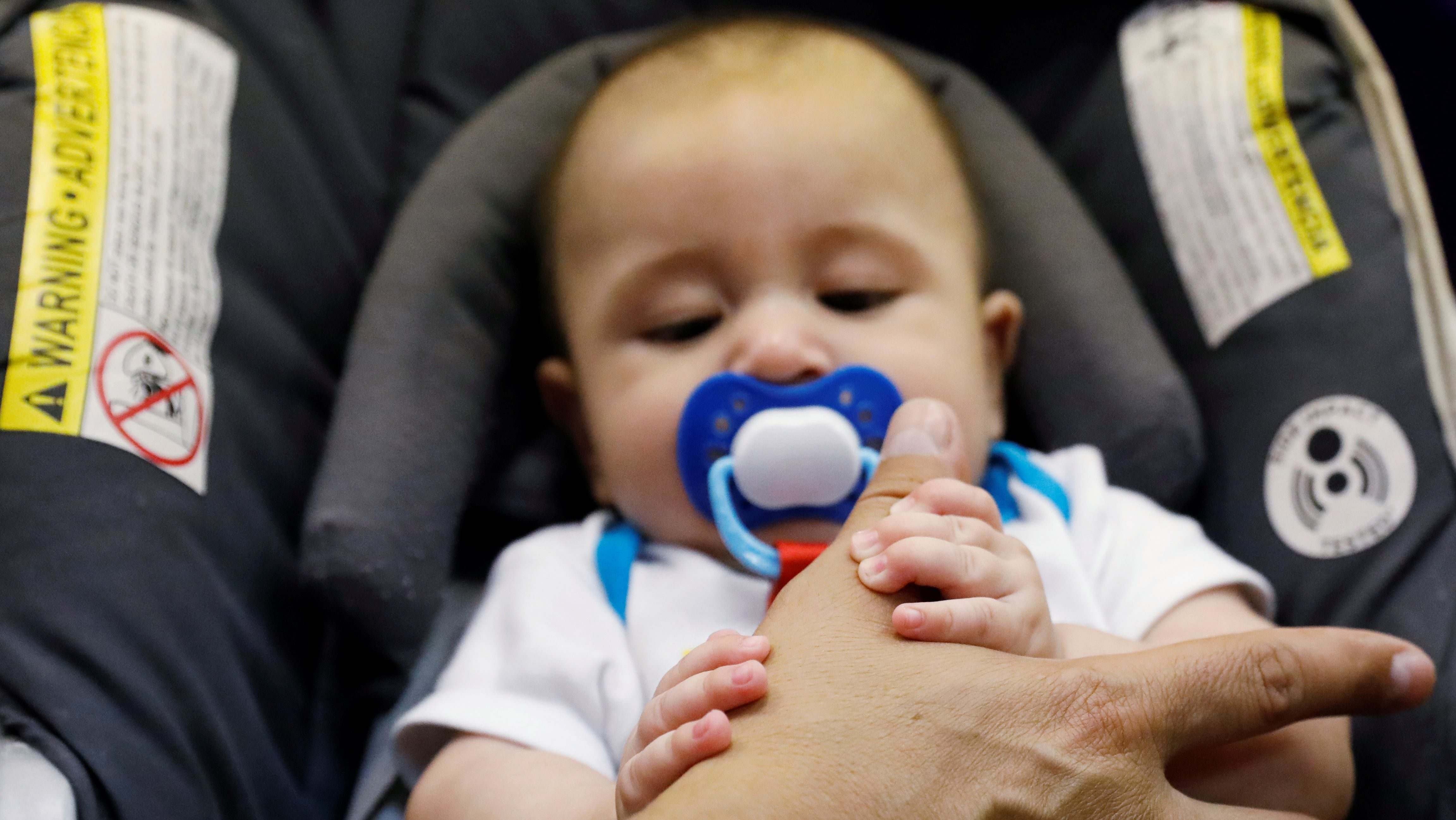 Marcelino Pizarro lets his baby son Matias play with his hand to quiet him during a church service near their home in El Paso, Texas, on May 9, 2018.