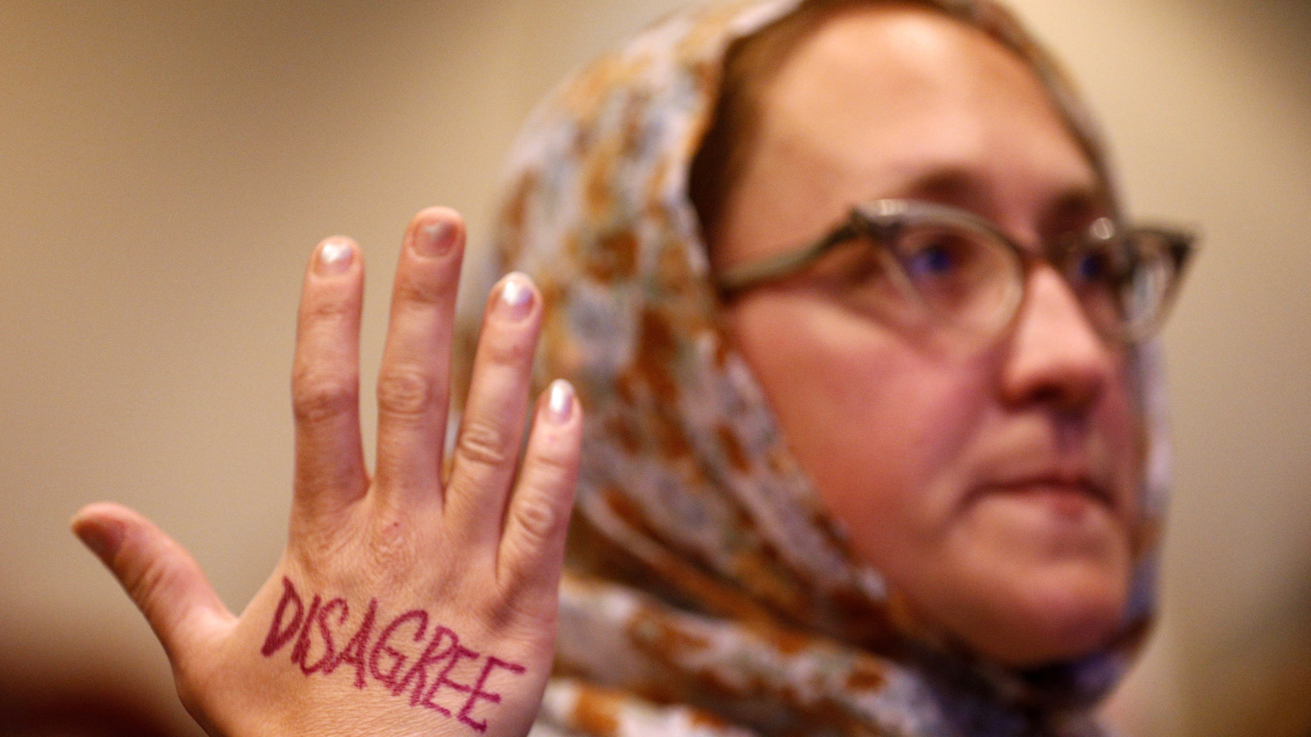 """Julia Grabowski holds up hand with the word """"disagree"""" on it at a New Orleans town hall meeting, 2017."""