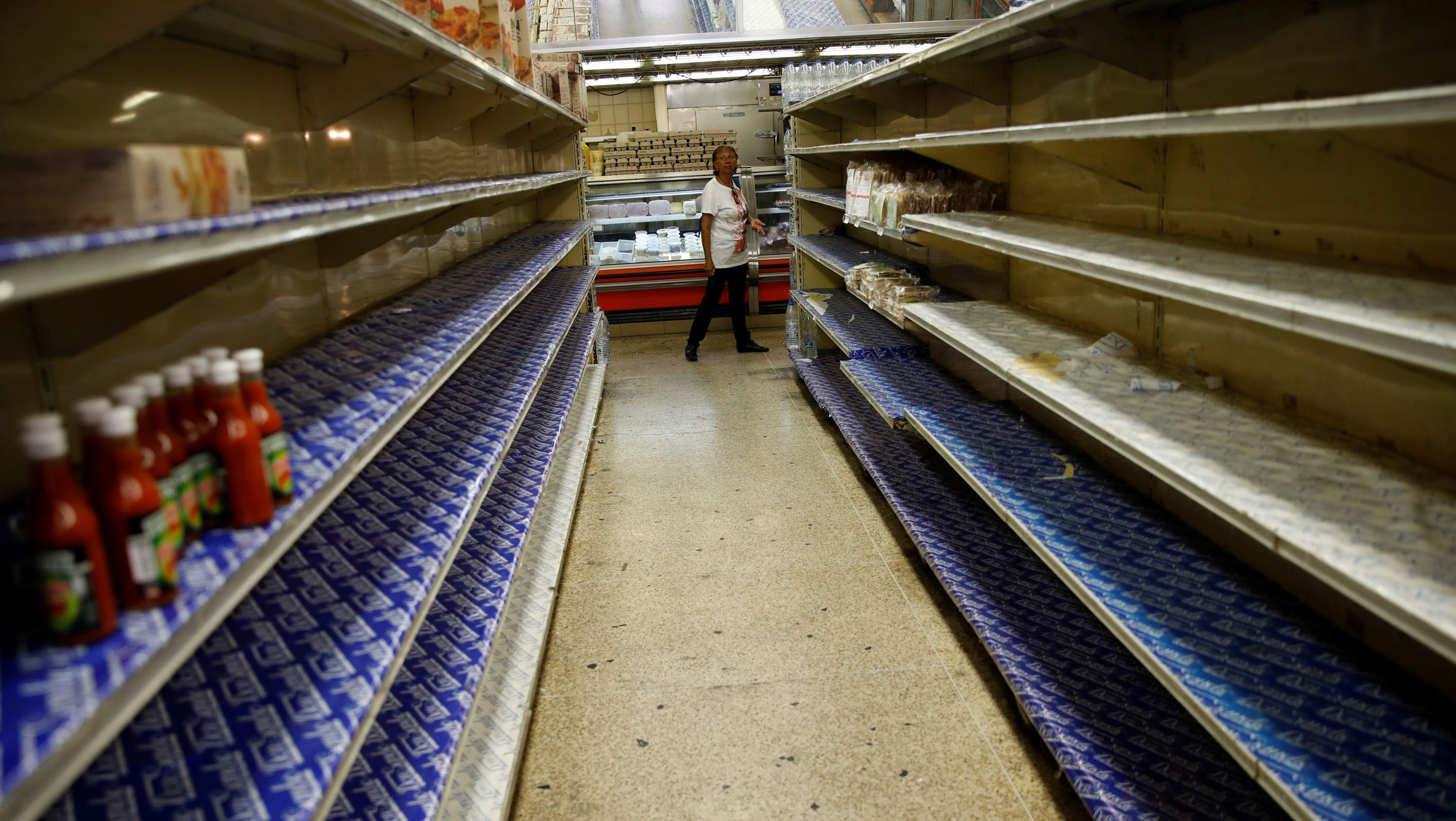 A woman looks at the almost empty shelves while she looks for groceries and goods in a supermarket in Caracas, Venezuela March 23, 2018.