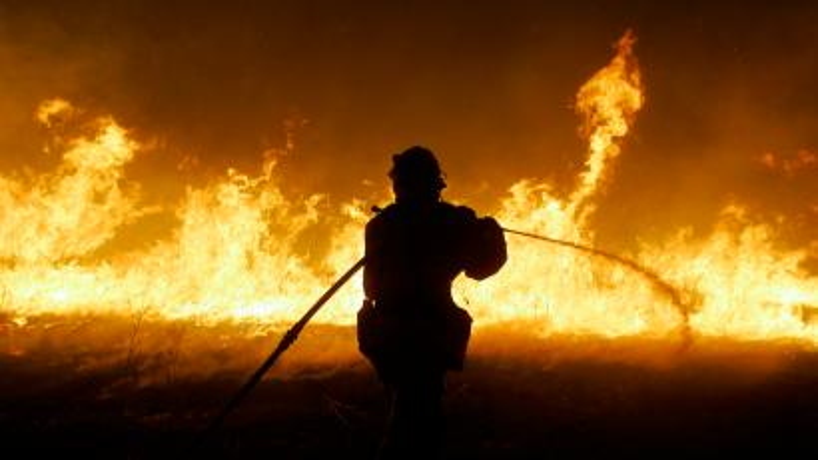 firefighter battles a fire