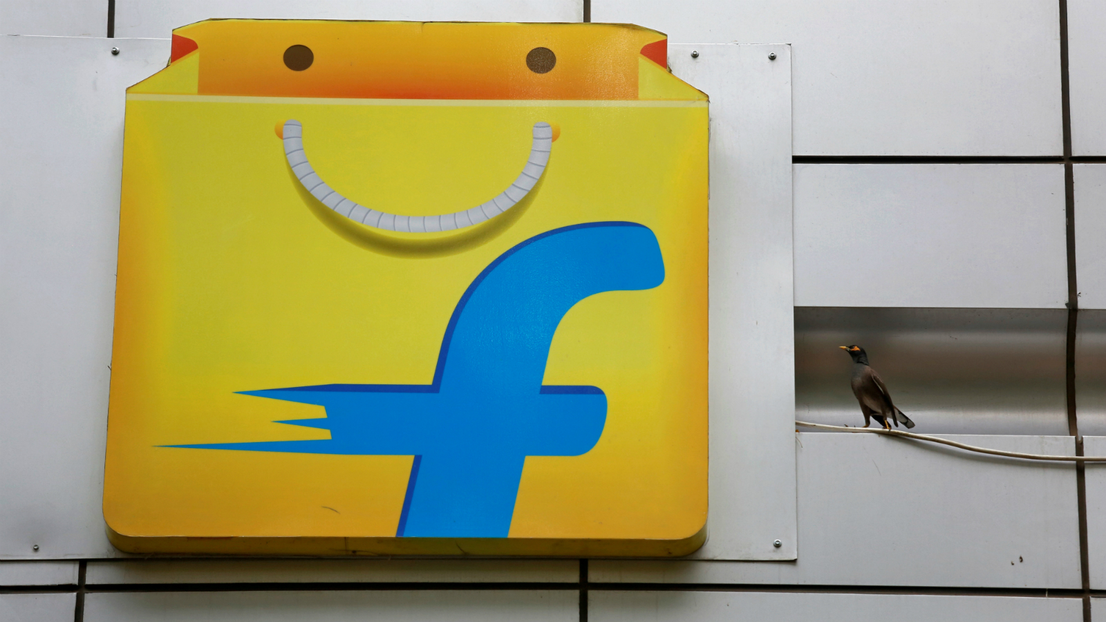 A Common myna sits next to the logo of India's e-commerce firm Flipkart installed on the company's office in Bengaluru, India April 12, 2018.