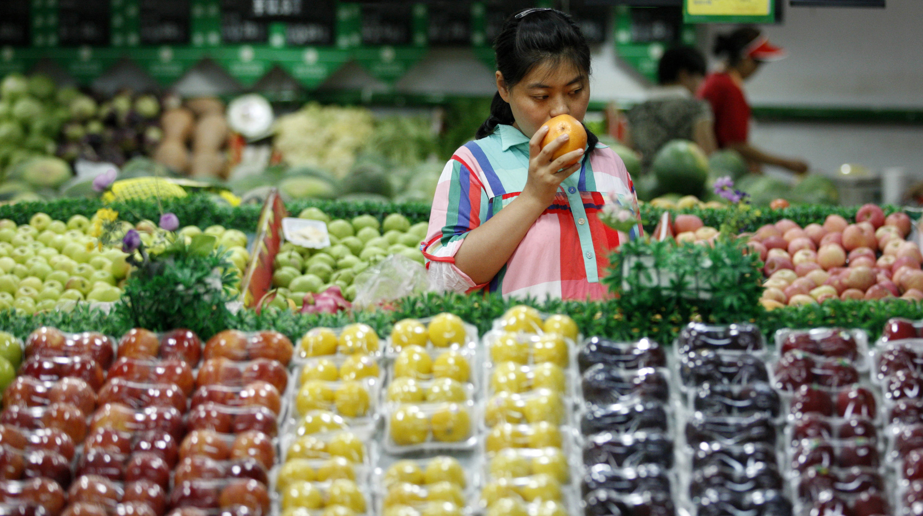 A woman selects fruits at a supermarket in Huaibei, Anhui province, July 9, 2014. China's consumer prices rose 2.3 percent in June from a year earlier while producer prices fell 1.1 percent, official data from the National Bureau of Statistics showed on Wednesday, largely in line with market expectations. REUTERS/Stringer (CHINA - Tags: BUSINESS FOOD SOCIETY) CHINA OUT. NO COMMERCIAL OR EDITORIAL SALES IN CHINA - GM1EA790UI301