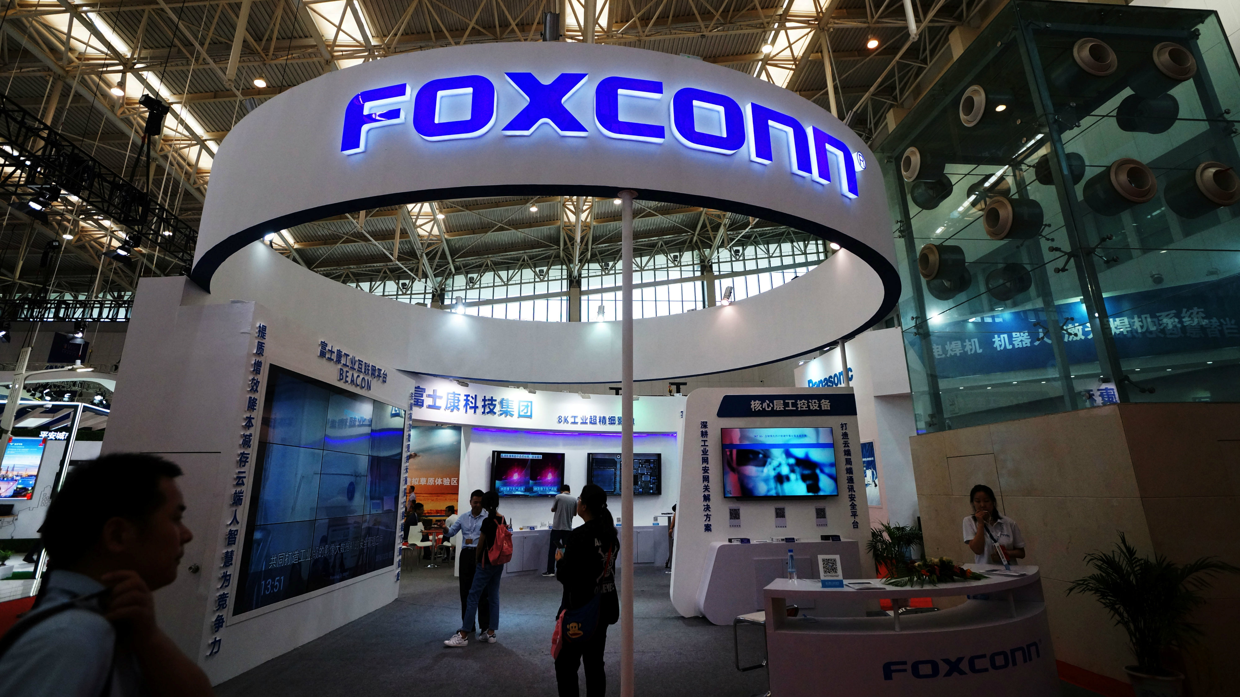 Visitors are seen at a Foxconn booth at the World Intelligence Congress in Tianjin, China May 19, 2018.