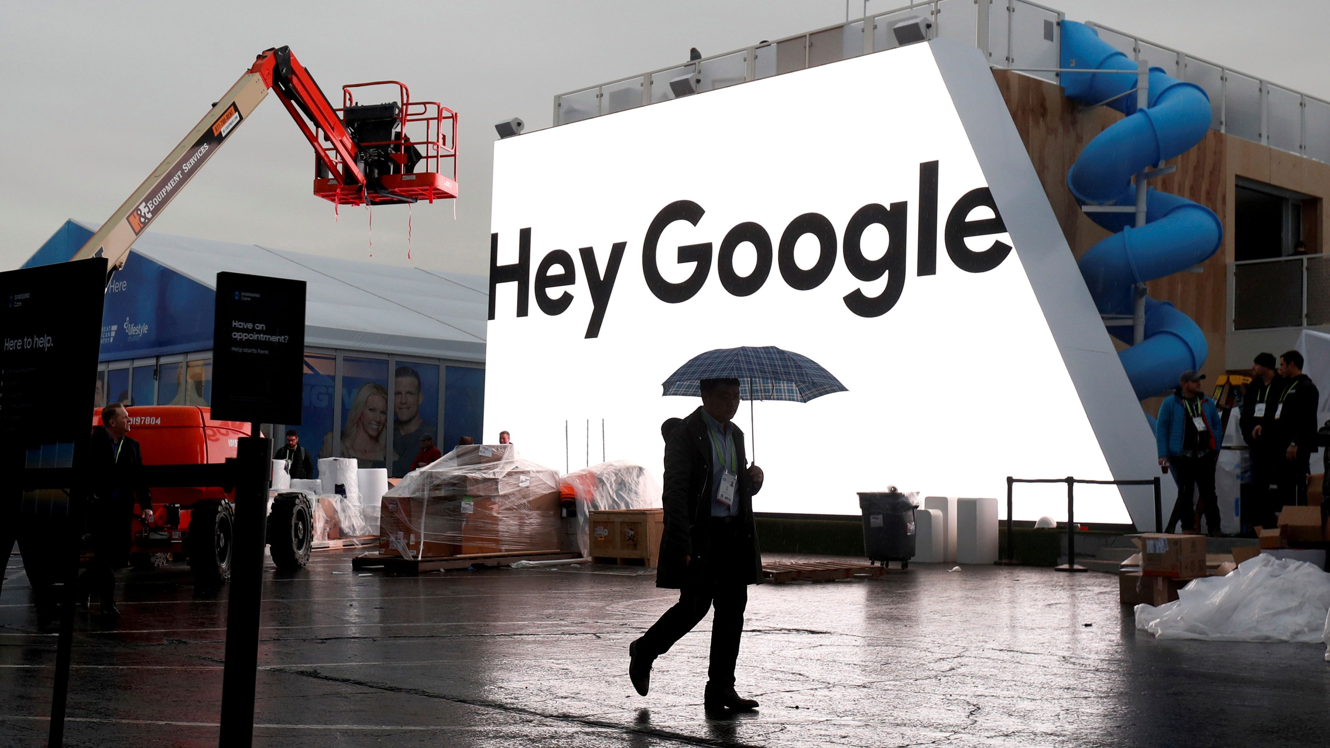 A man walks by the Hey Google booth under construction at the Las Vegas Convention Center in preparation for the 2018 CES in Nevada.
