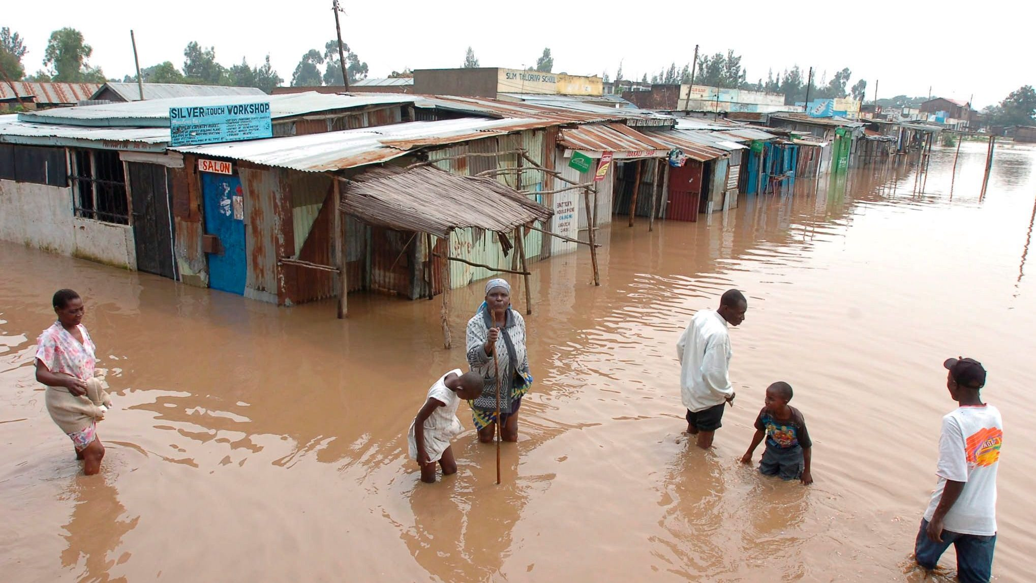 Villagers go about their business in a flooded market centre in Kisumu, about 400km west of the capital Nairobi in Kenya on Saturday 30 December 2006. Heavy rains continue to cause havoc in Kenya and parts of East Africa.