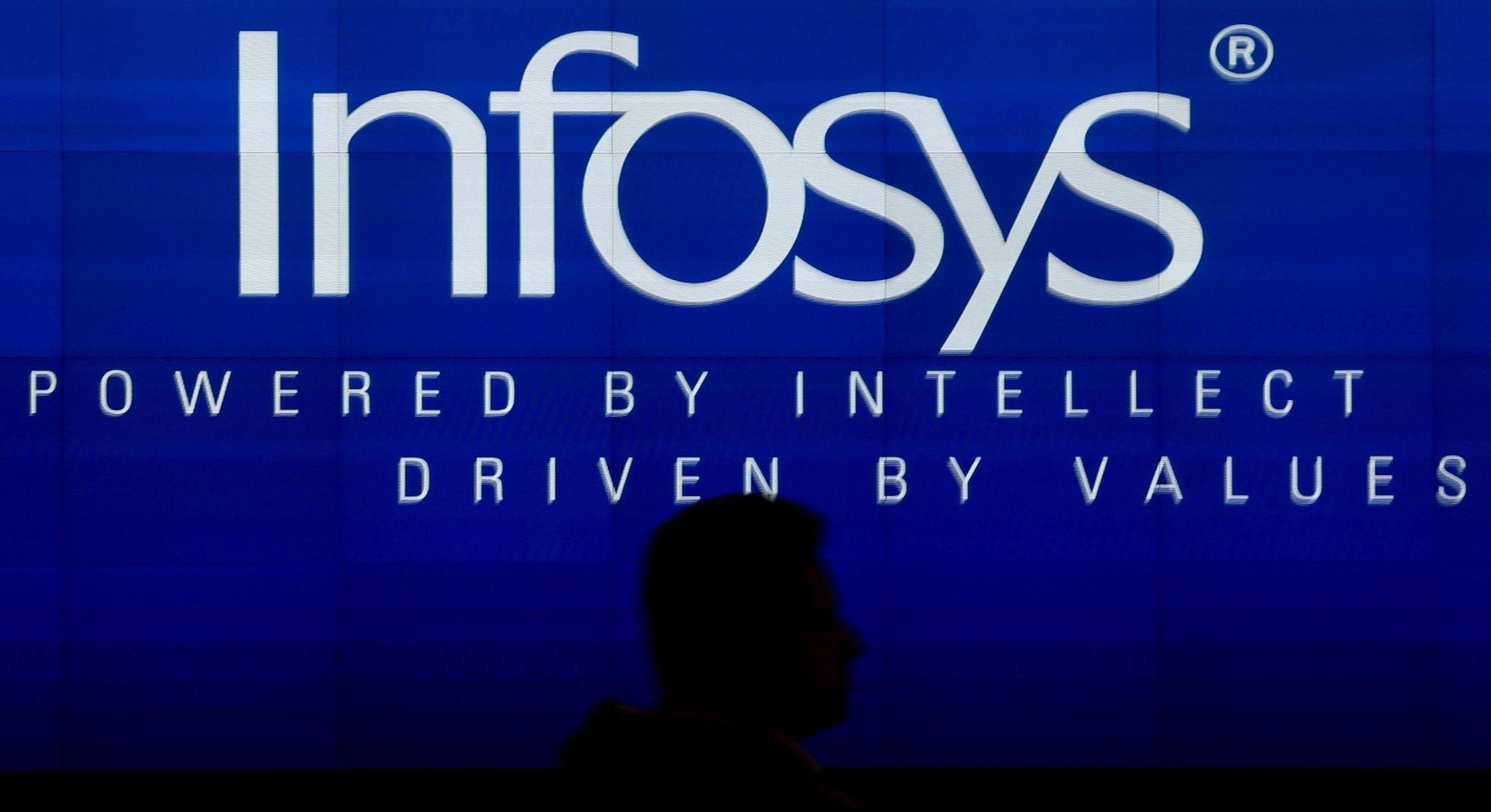 epa06433506 Shillouted Indian software professional walks down in front of Infosys logo at Indian multinational corporation Infosys Limited, during Q3 results at the Infosys headquarters, in Bangalore, India, 12 January 2018. India's second-biggest IT services exporter Infosys Ltd posted a 38.3 per cent jump in third-quarter profit, helped by tax benefits from the firm's deal with US Internal Revenue Service.