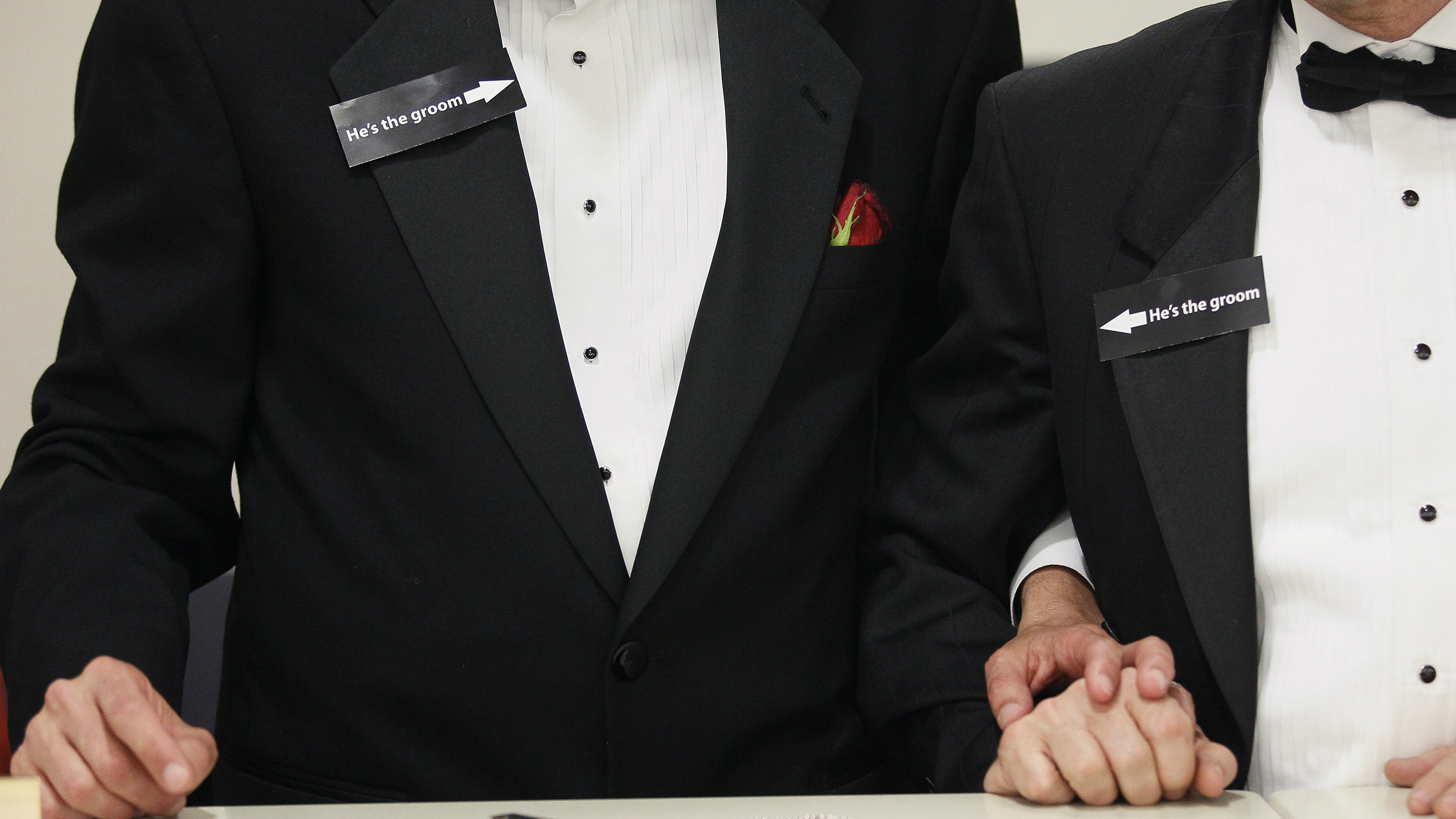 "Two men, both wearing signs that read ""he's the groom"", hold hands shortly after midnight after getting a civil union when Colorado's civil union law went into effect in Denver May 1, 2013. Colorado joined eight states that recognize civil unions or domestic partnerships in lieu of gay marriage, according to the Human Rights Campaign."