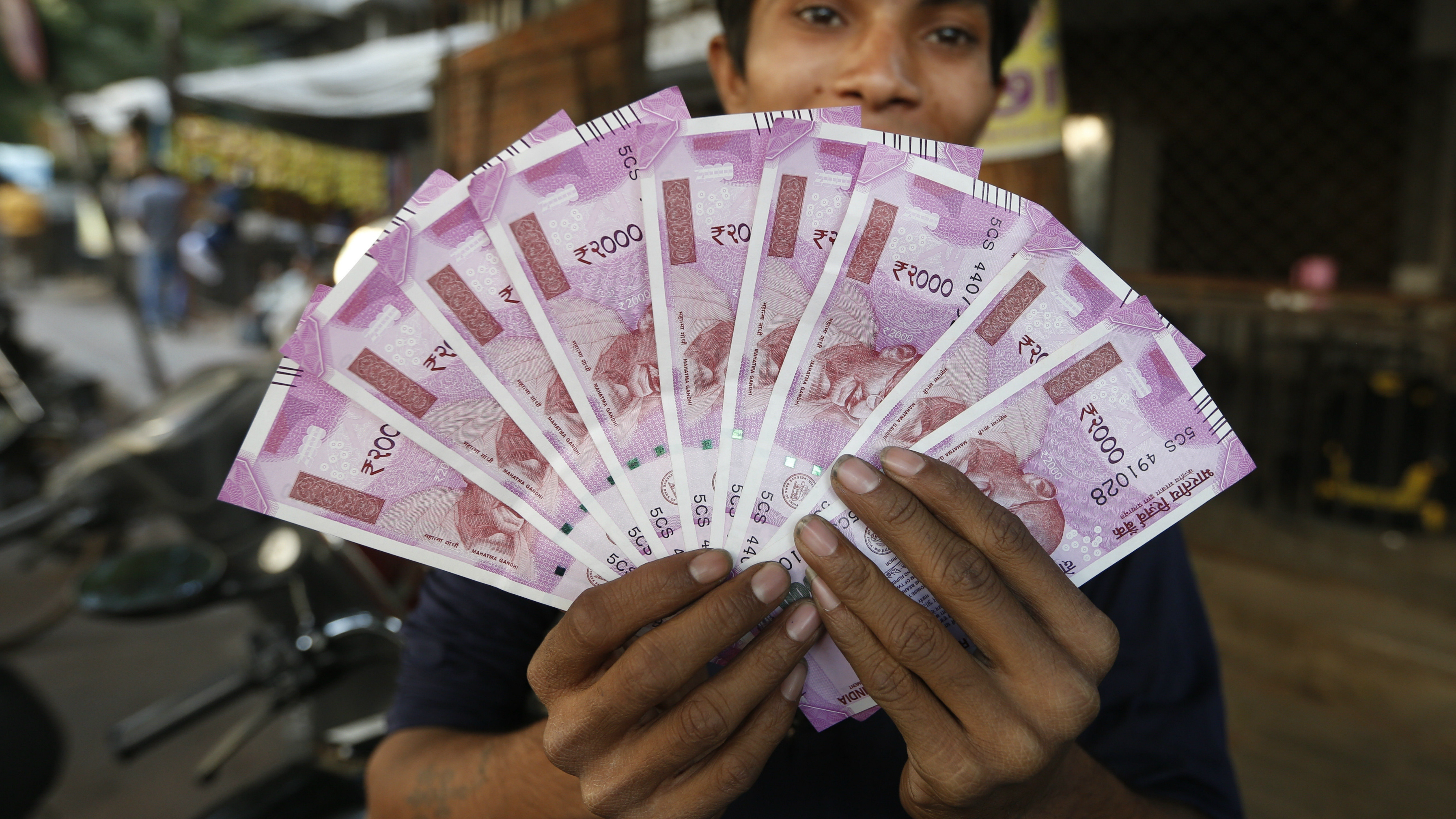 An Indian man holding rupee notes,