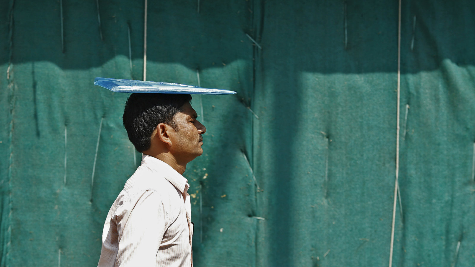 A man keeps a file folder on his head to protect himself from the sun during a hot summer day in New Delhi, India, June 8, 2015. Temperature in New Delhi on Monday is expected to reach 43 Celsius (109.4 degree Fahrenheit), according to India's metrological department website.