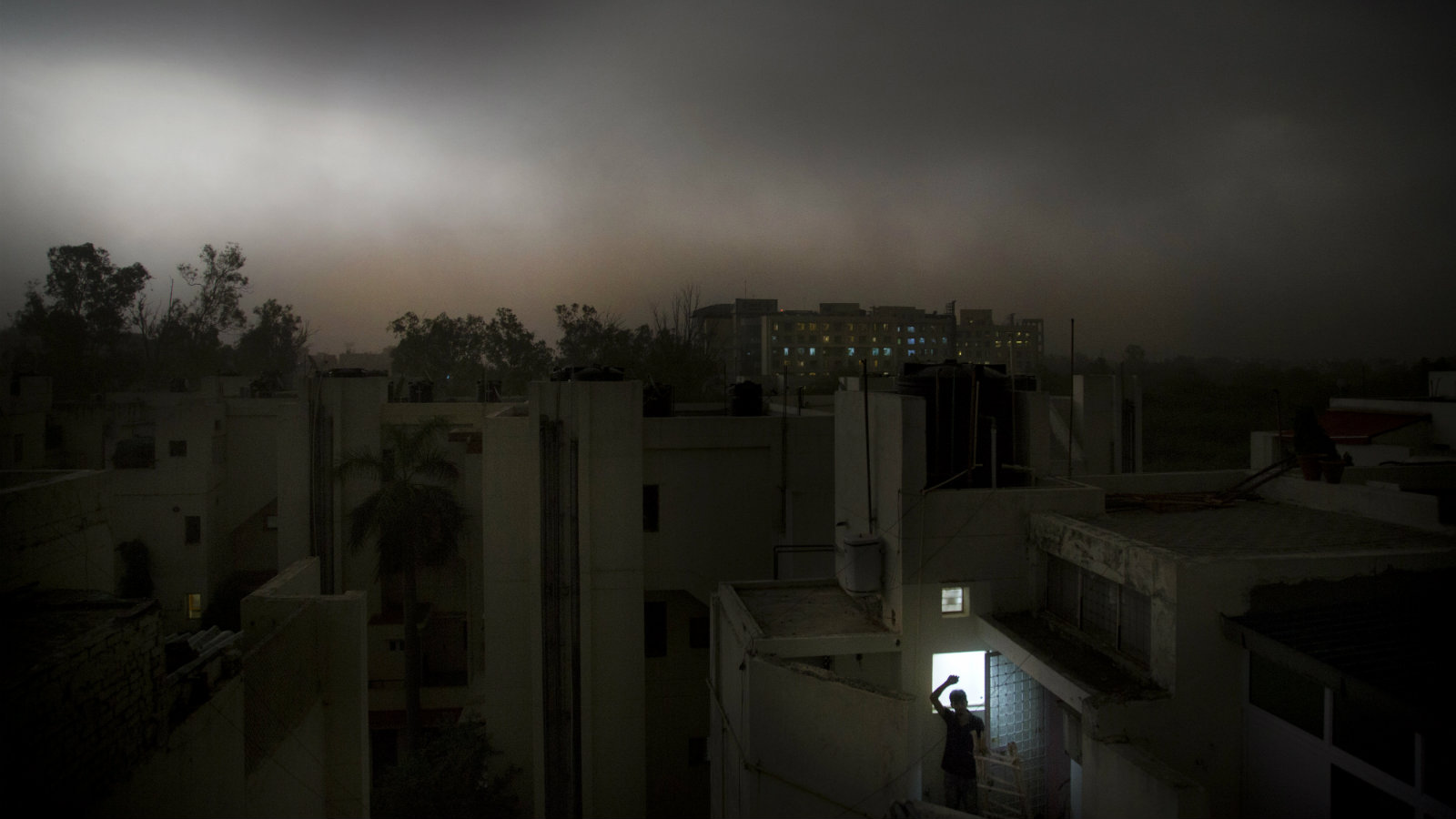 An Indian man stands on the balcony of his apartment during a suddens storm accompanied by rain in New Delhi, India, Sunday, May 13, 2018. The monsoon season is nearly six weeks away in India.