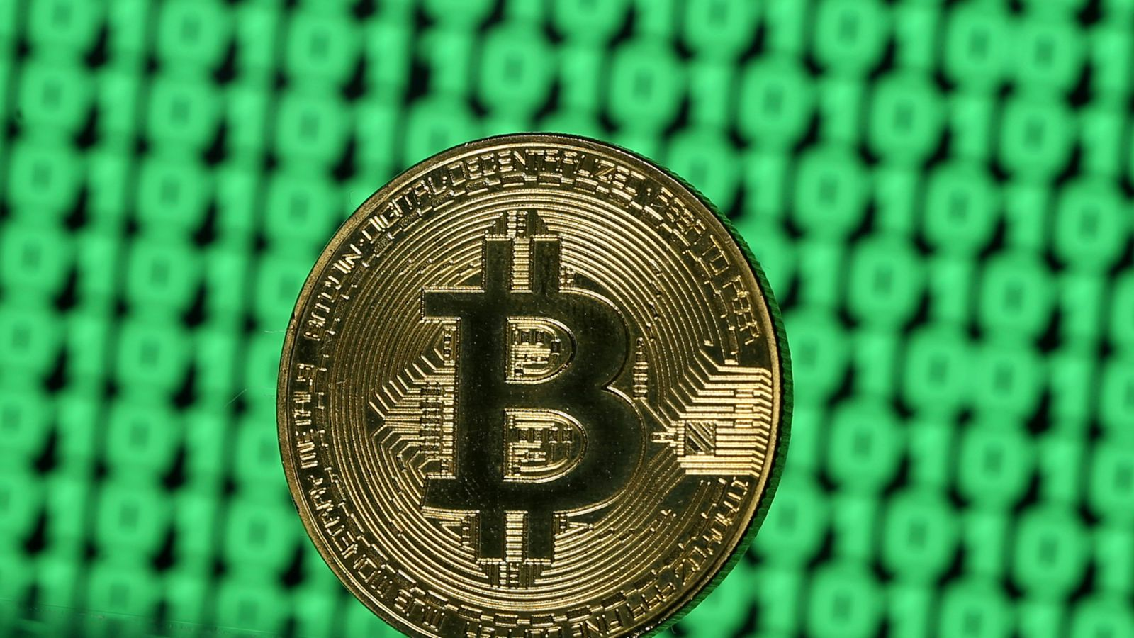 A token of the virtual currency Bitcoin is seen placed on a monitor that displays binary digits in this illustration picture, December 8, 2017.