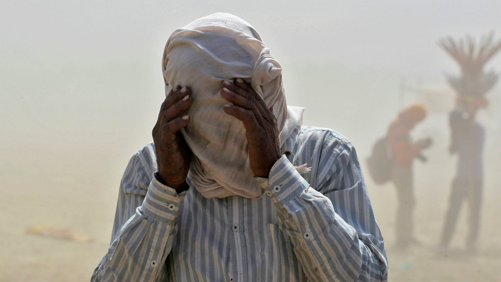 A man covers his face as he walks through a dust storm on the banks of the Ganga river in Allahabad, India, April 12, 2016