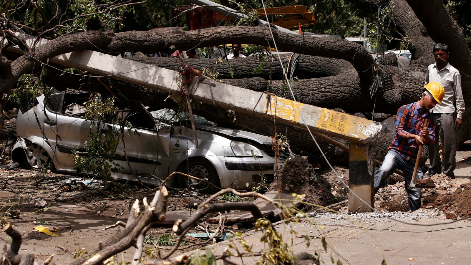 Electricity department workers remove damaged poles stuck under uprooted trees after Tuesday night's dust storm in New Delhi, India, May 16, 2018.