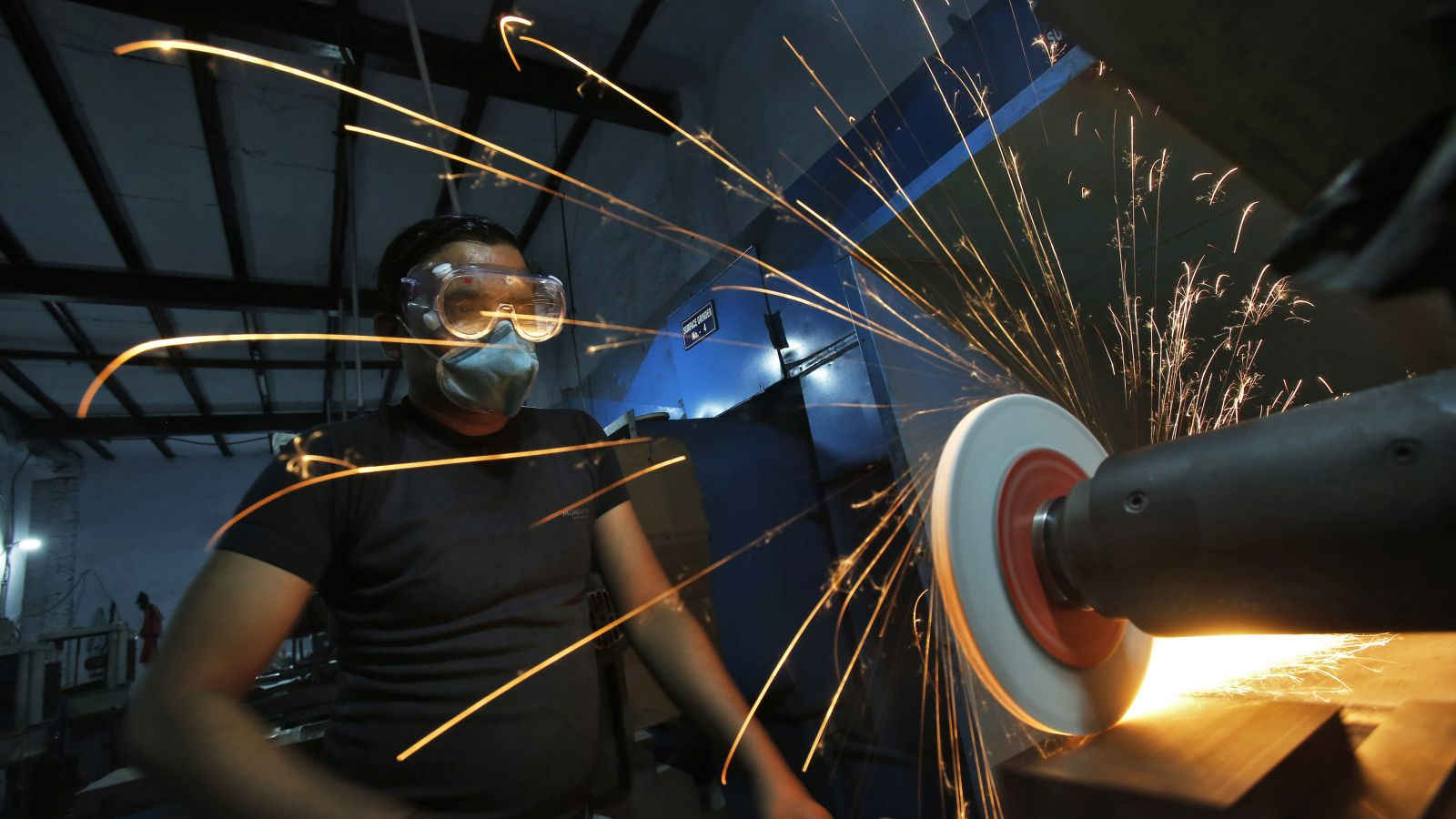 A worker operates a lathe machine as he makes a steel cutter at a manufacturing unit in Noida, on the outskirts of New Delhi November 3, 2014. Indian factory activity expanded at a modest pace in October, as stronger demand led manufacturers to add jobs for the first time in four months and allowed them to raise prices, a business survey showed on Monday.