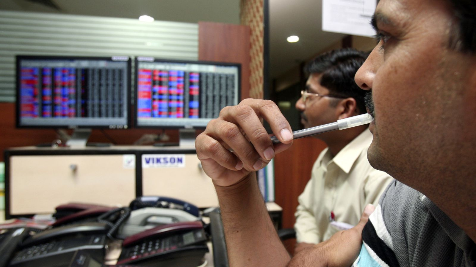 Investors watch the share index at a local share trading market in the northern Indian city of Chandigarh November 12, 2008. India's main stock index provisionally closed 2.94 percent lower on Wednesday. The 30-share main BSE index provisionally closed 288.92 points lower at 9550.77