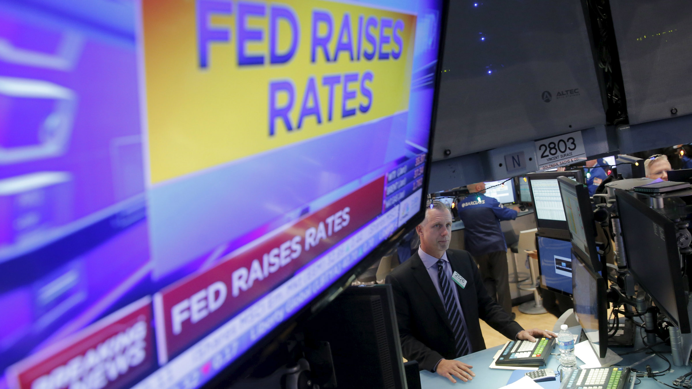 "TV showing chyron ""Fed raises rates"" on a trading floor"