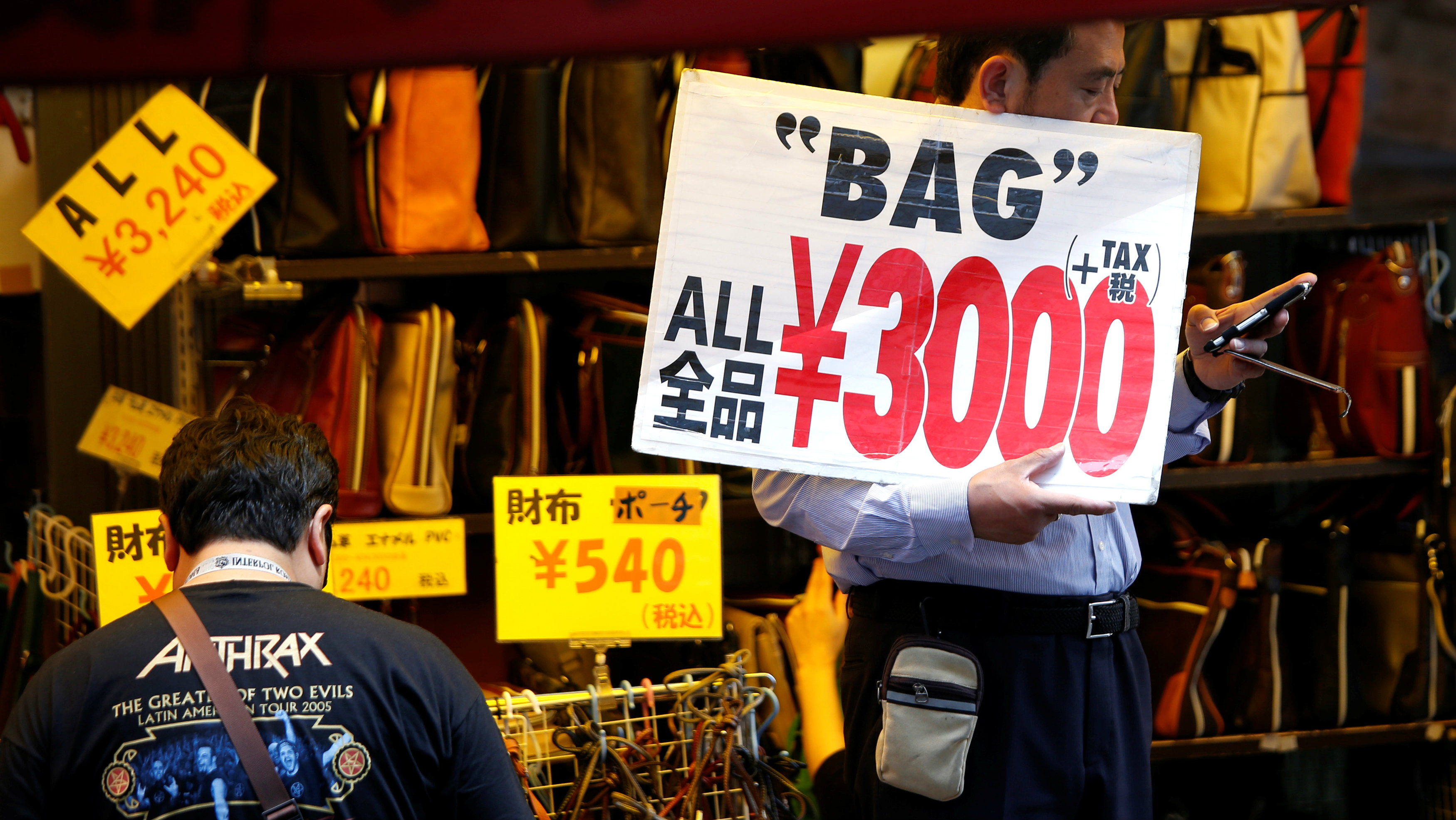 A shop employee holds a placard to attract costomers in Tokyo, Japan