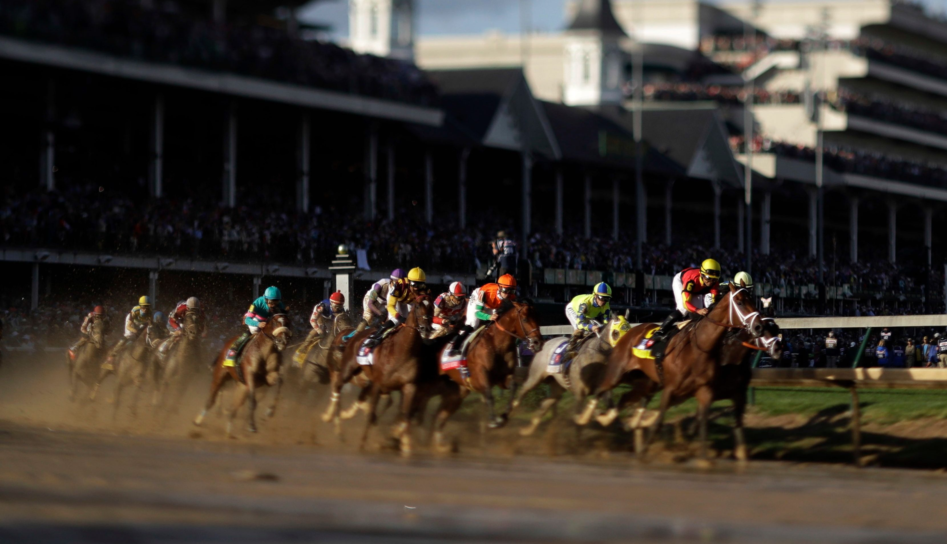In this image made with a tilt-shift lens, horses run through the first turn during the 143rd running of the Kentucky Derby horse race at Churchill Downs Saturday, May 6, 2017, in Louisville, Ky.