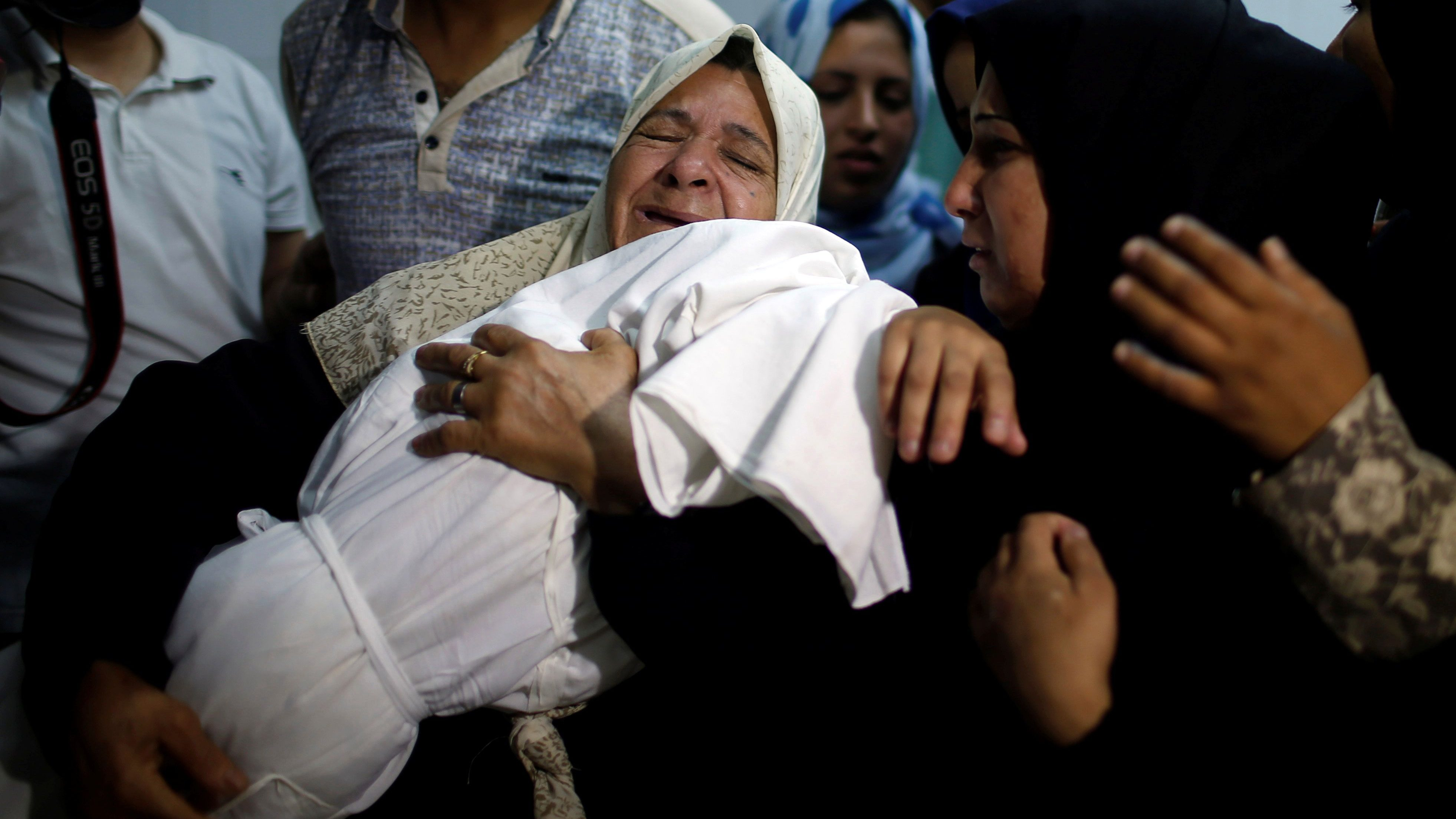 A relative mourns as she carries the body of 8-month-old Palestinian infant Laila al-Ghandour during her funeral in Gaza City on May 15, 2018.