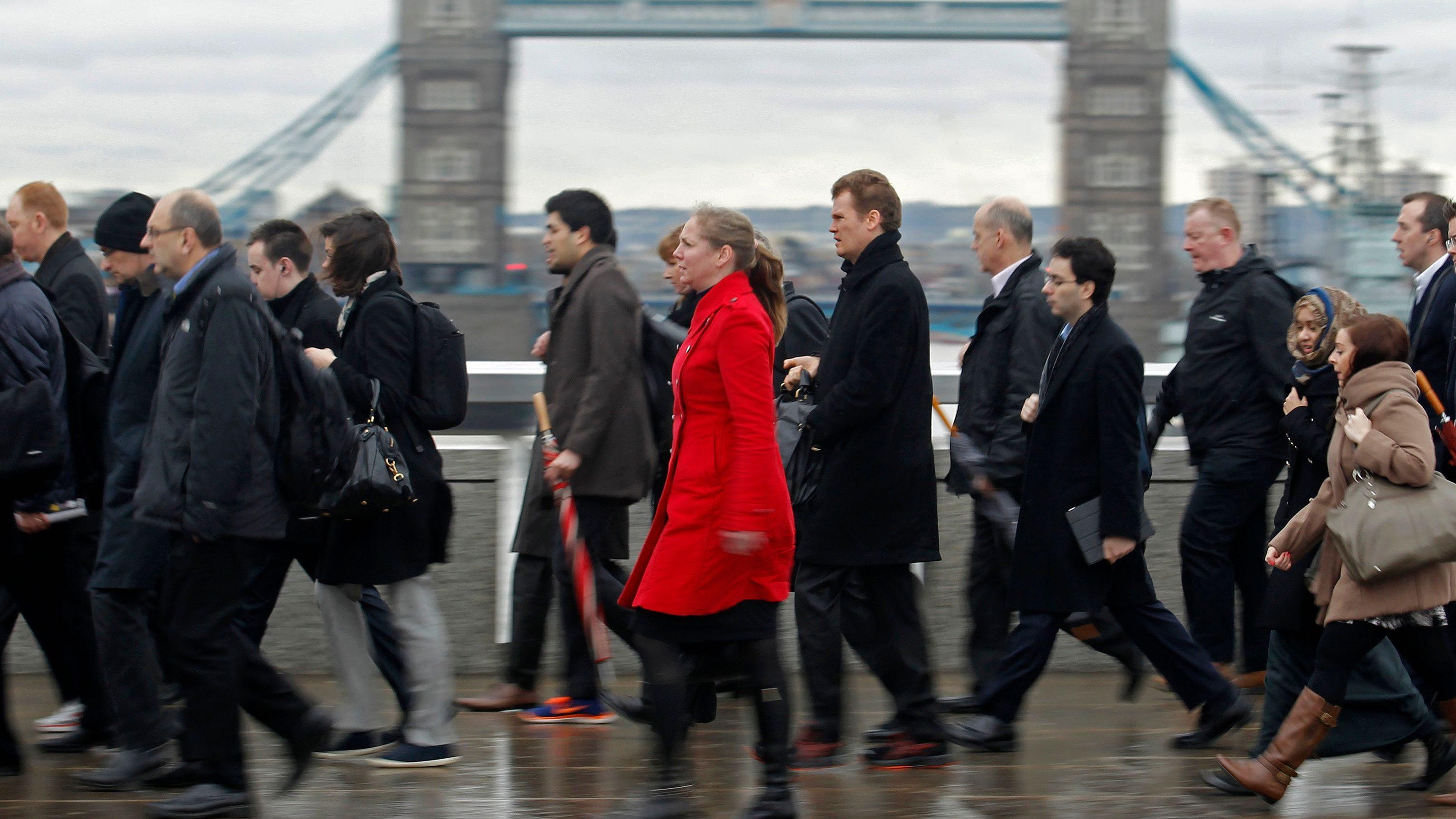 Rush hour workers pass Tower Bridge in London