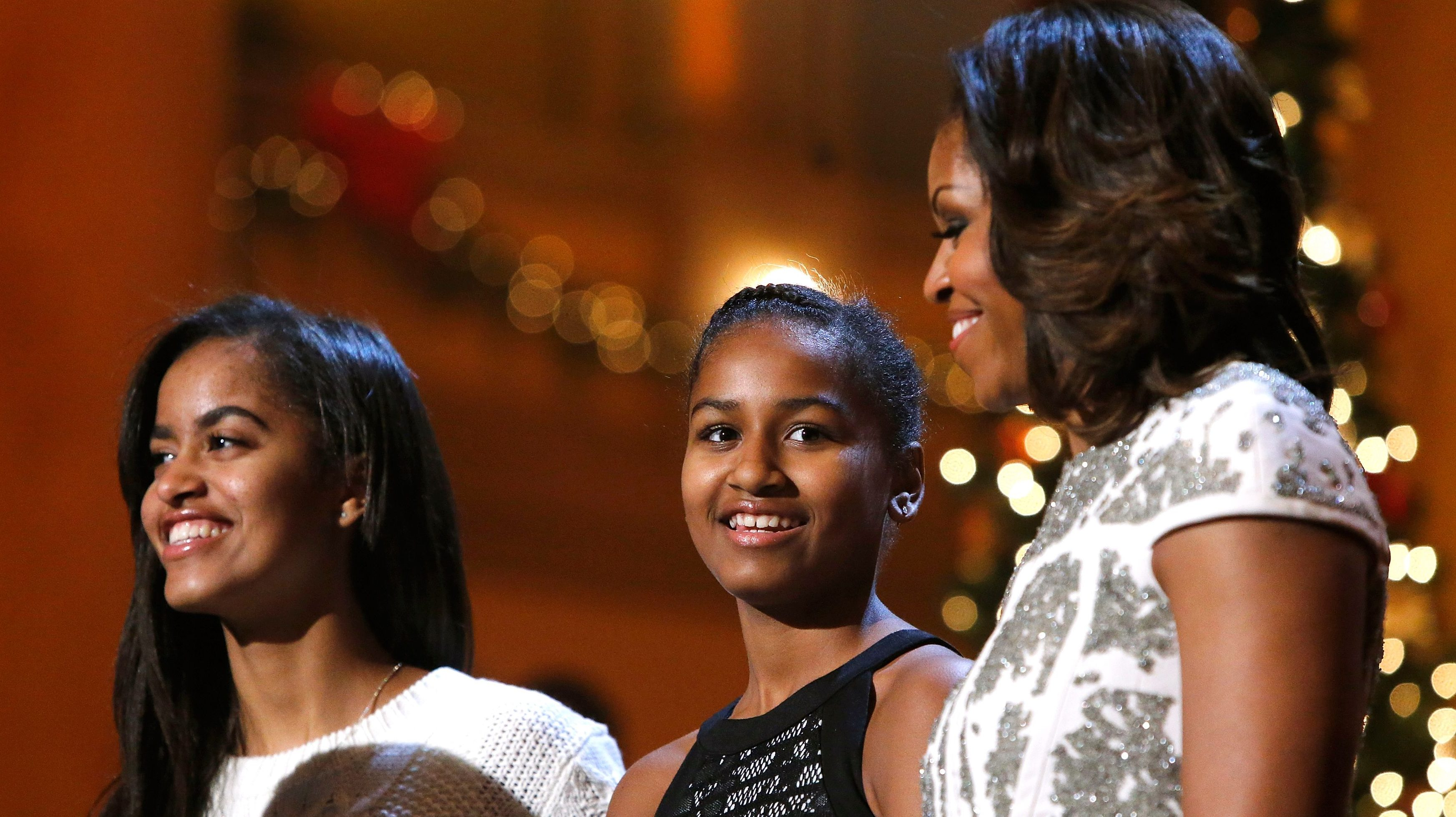 U.S. first lady Michelle Obama (R) and daughters Malia (L) and Sasha stand onstage during remarks by President Barack Obama for a taping of the Christmas in Washington television benefit program at the National Building Museum in Washington December 15, 2013.