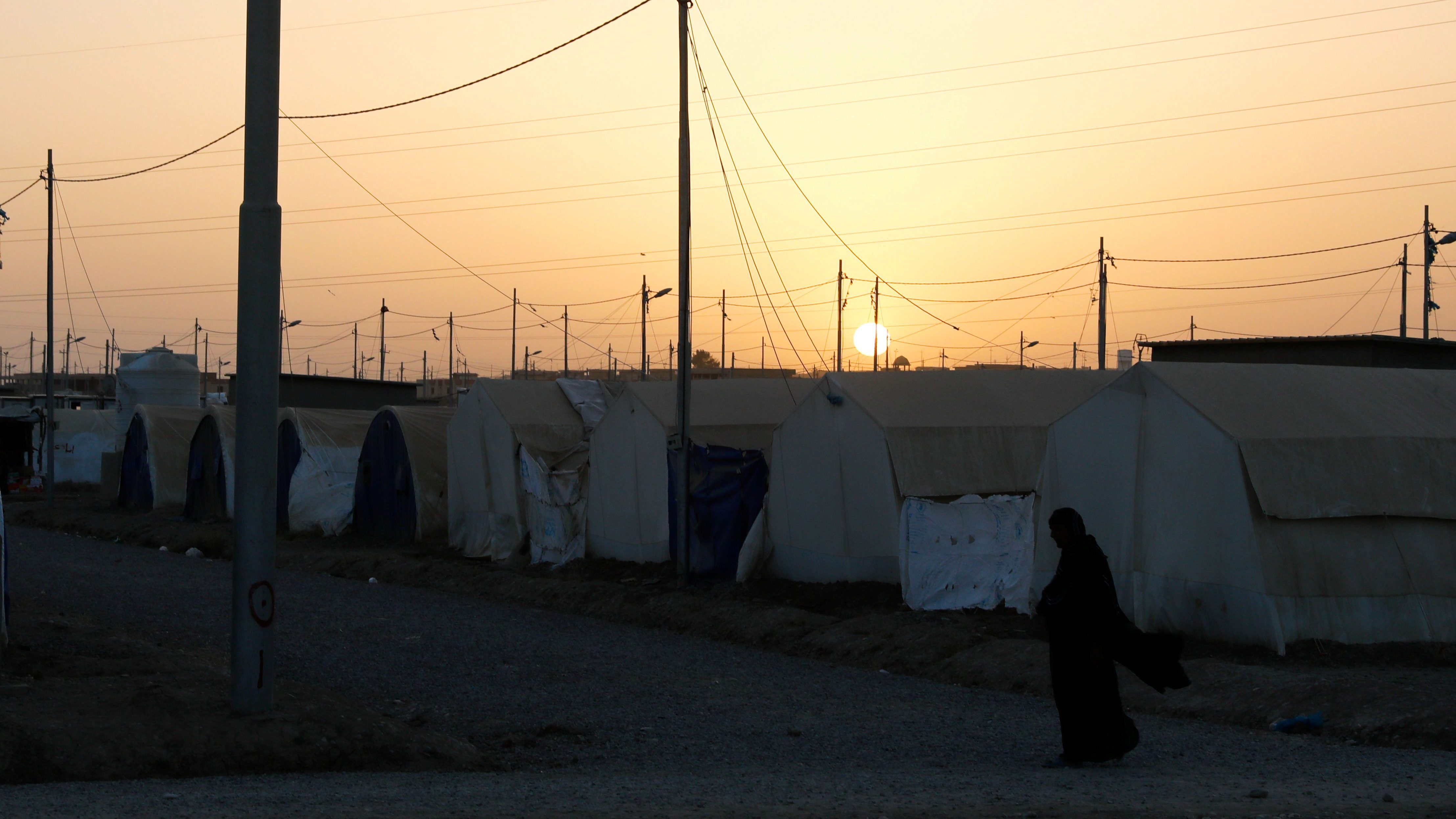 A displaced Iraqi woman from Mosul walks towards her family's tent for their Iftar, during the Muslim holy month of Ramadan at a refugee camp al-Khazir in the outskirts of Erbil, Iraq