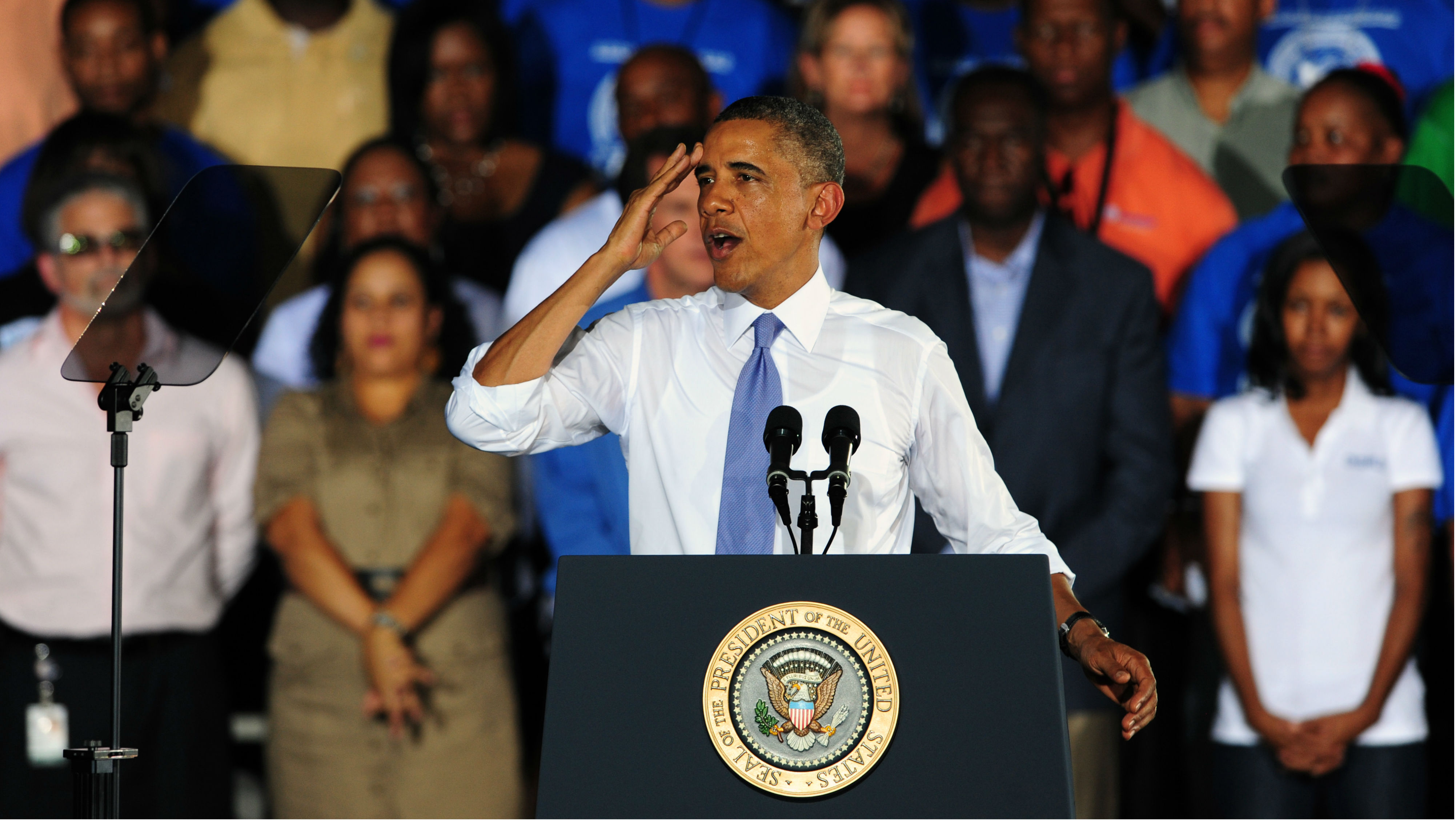 Obama giving a speech and wiping sweat off his face.